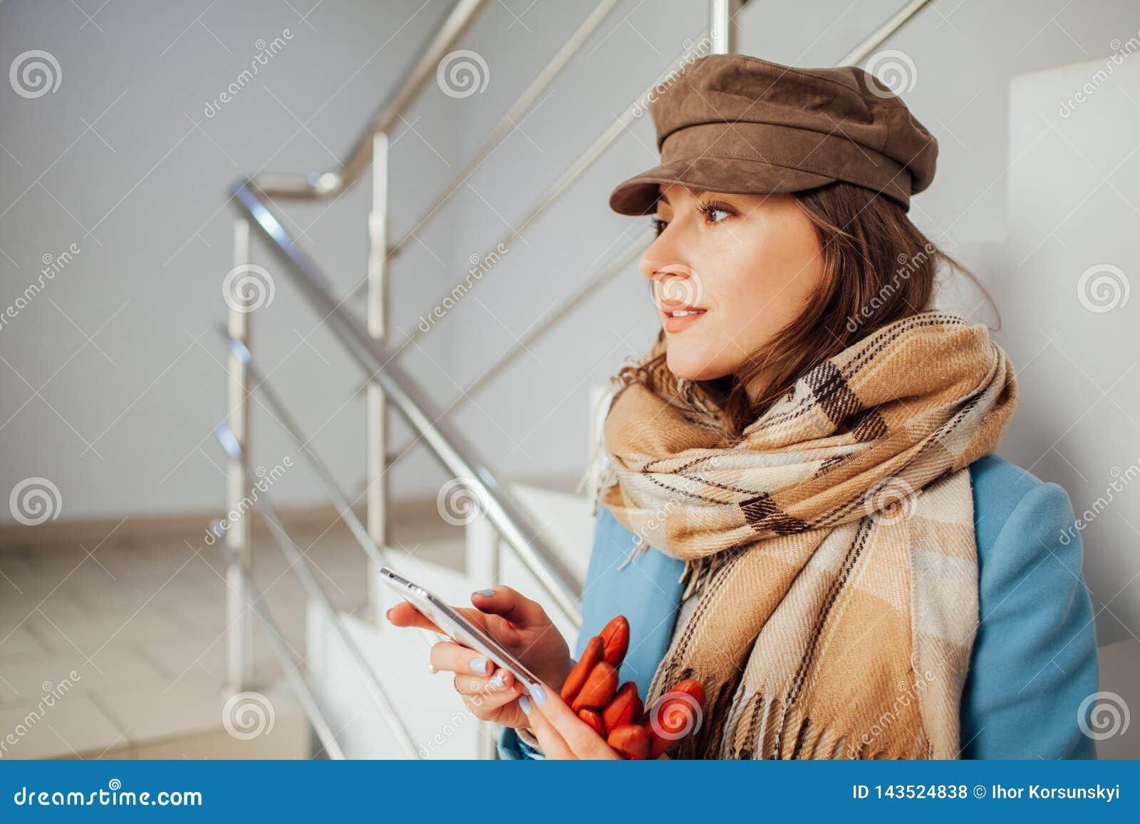 Donna di affari nei supporti del cappotto sulle scale nel centro commerciale con lo smartphone Acquisto Modo