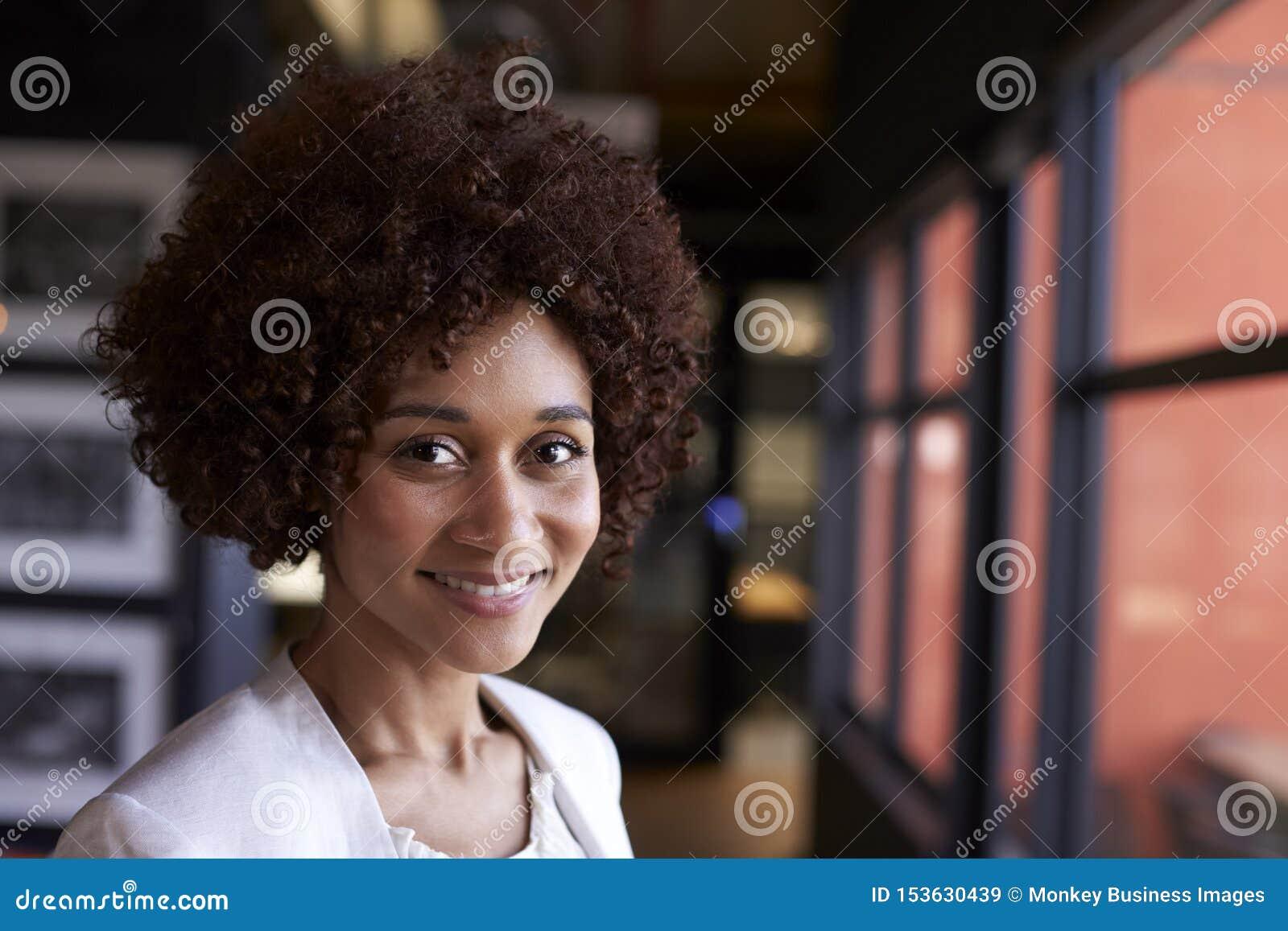 Donna di affari nera millenaria che sorride alla macchina fotografica dalla finestra in un ufficio, fine su