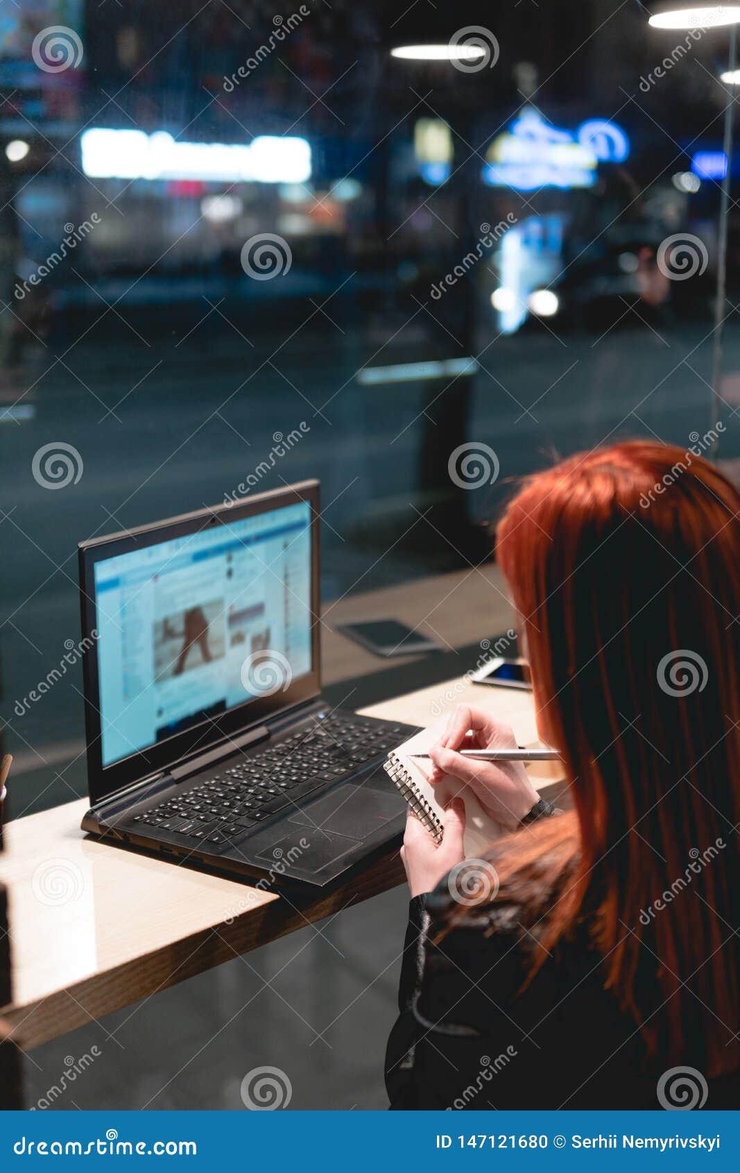 Donna di affari, ragazza che tiene una penna, scrivente in un taccuino, computer portatile in caff?, smartphone, penna, computer