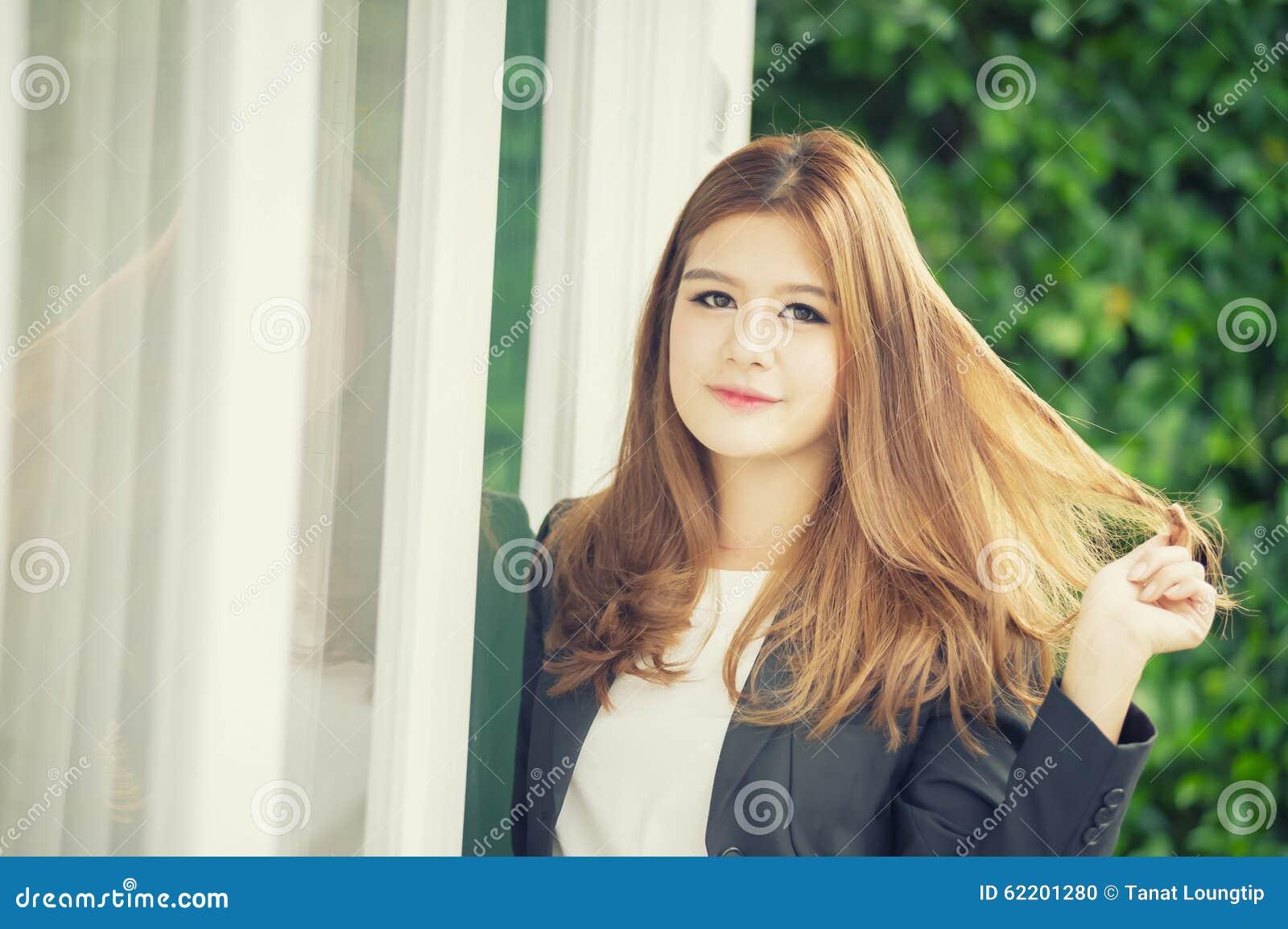 Donna di affari sicura dell Asia giovane in vestito che si tiene per mano sui capelli