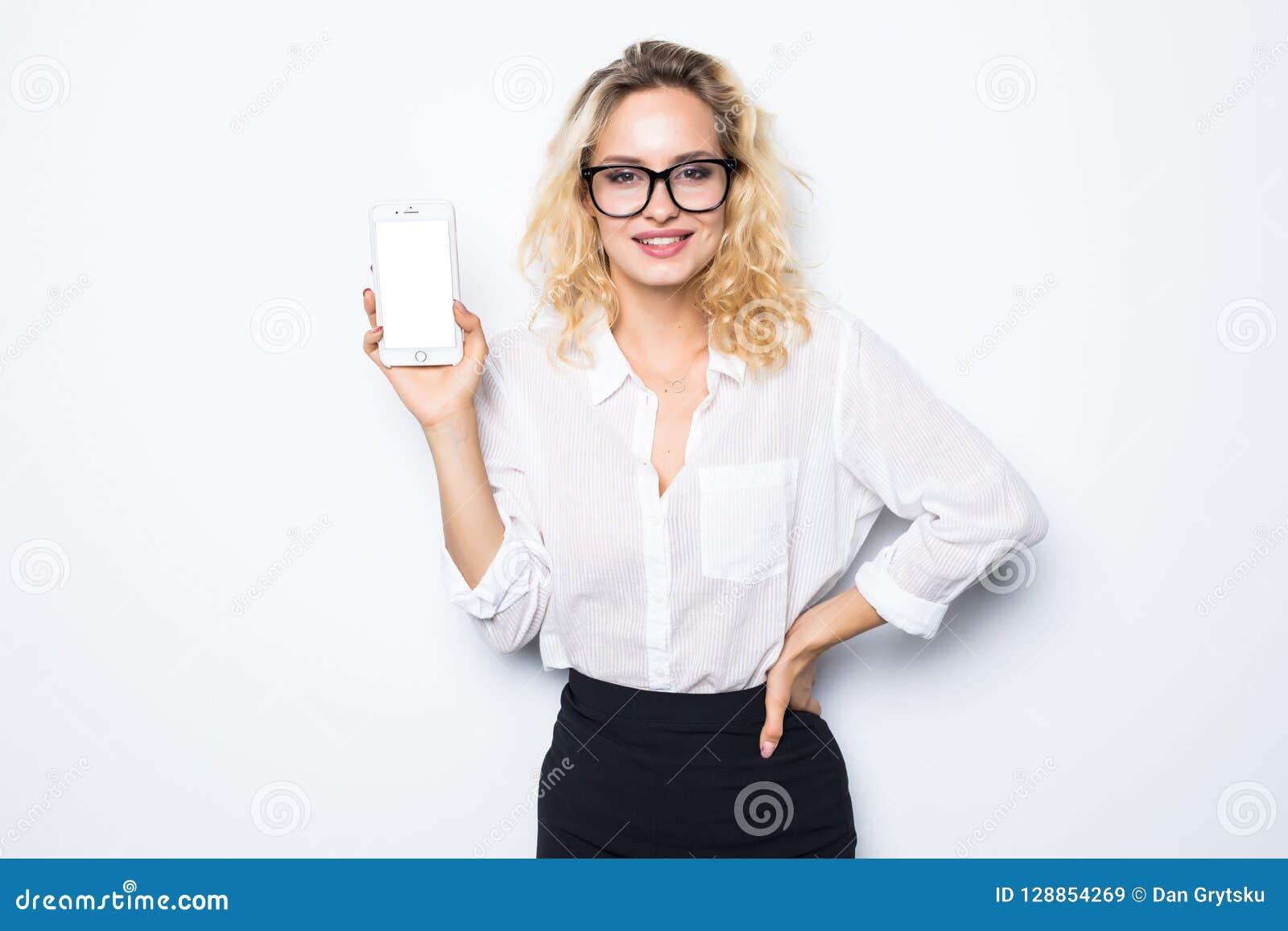 Donna di affari sorridente che mostra lo schermo in bianco dello smartphone sopra fondo bianco