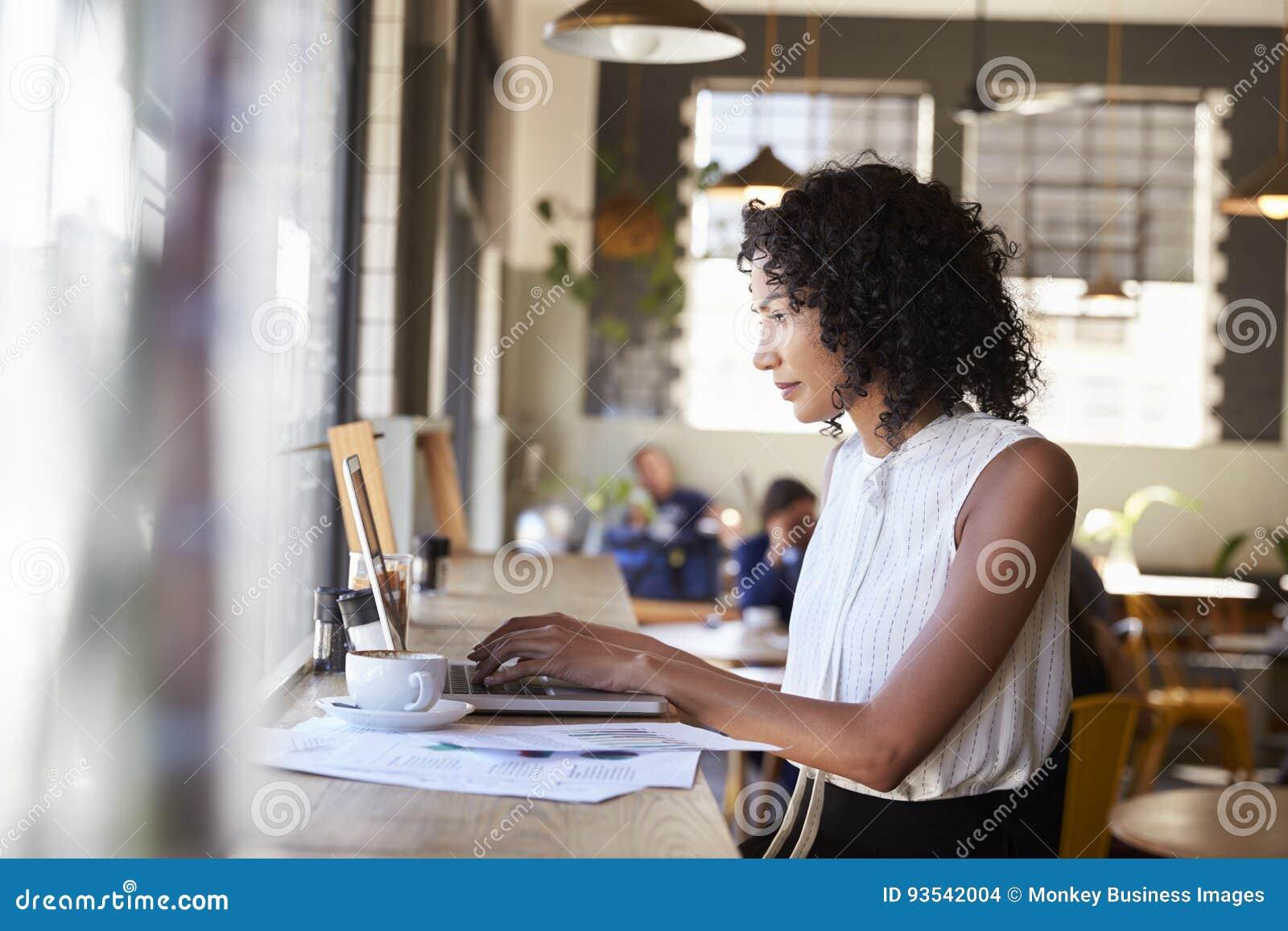 Donna di affari By Window Working sul computer portatile in caffetteria