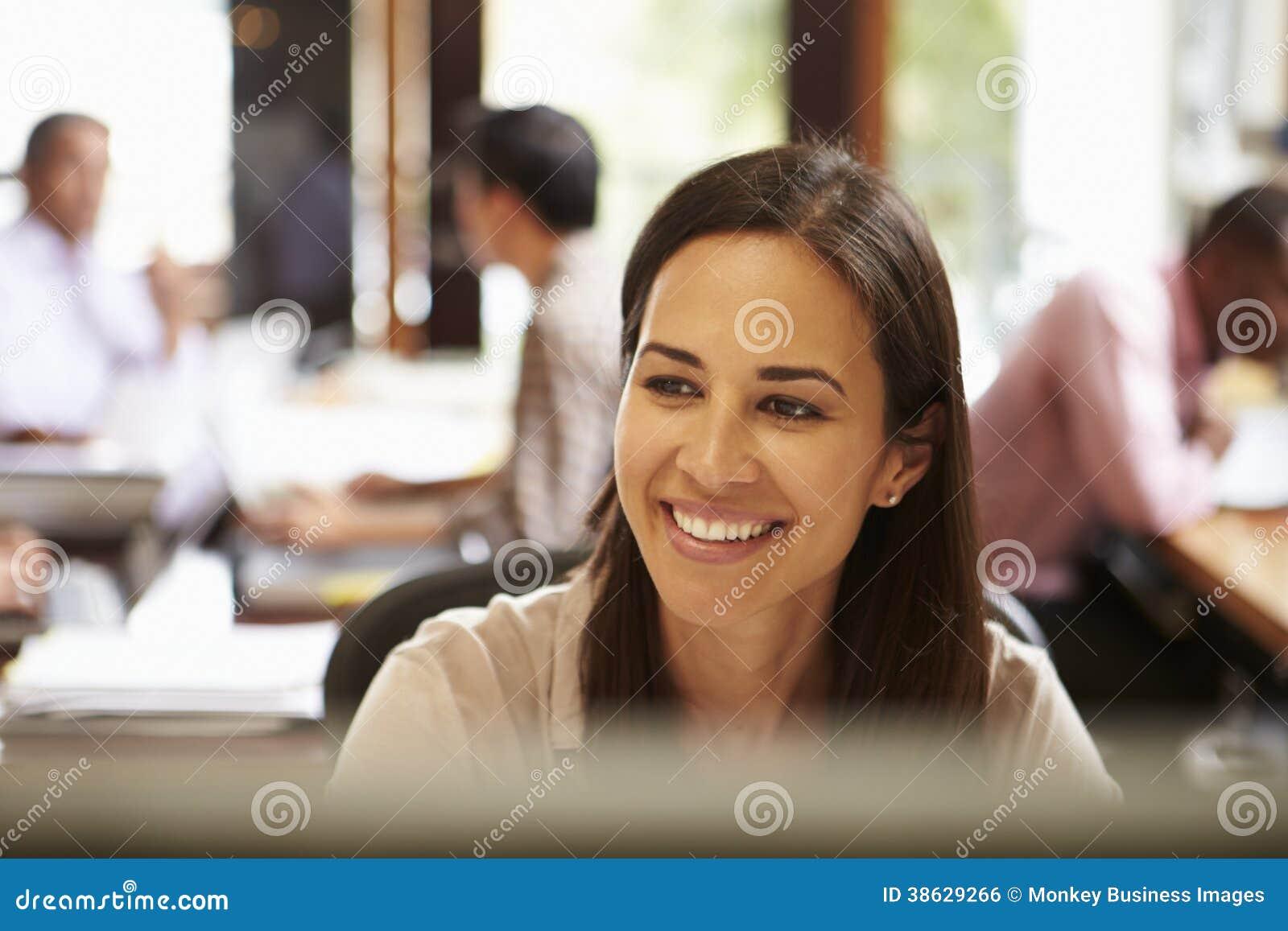 Donna di affari Working At Desk con la riunione nel fondo