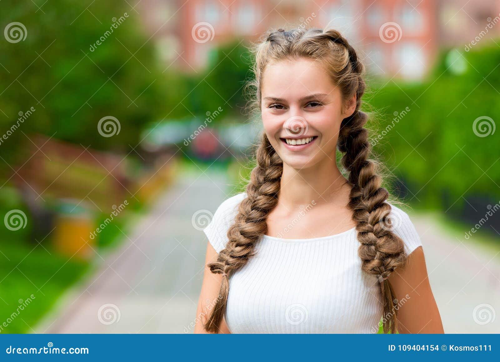 Donna di 20 anni felice della st del primo piano in una maglietta bianca con due