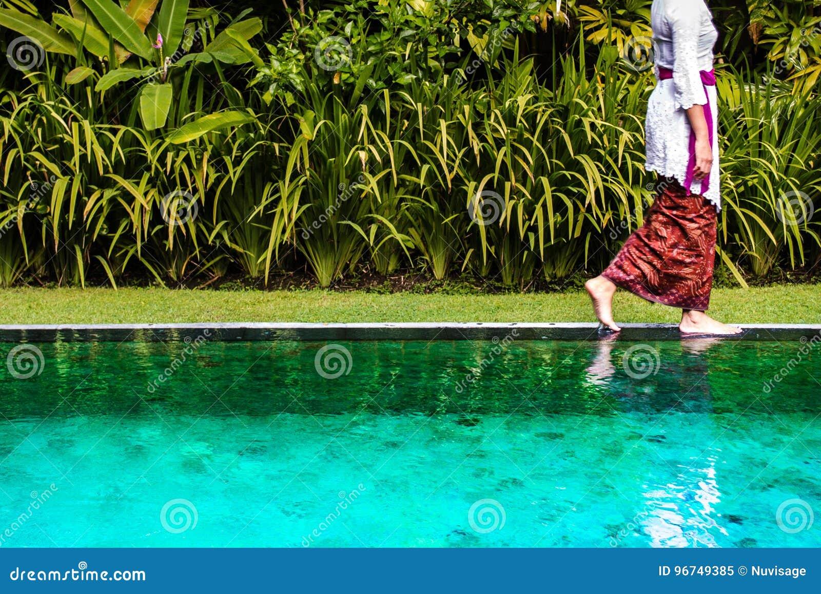 Donna di balinese che cammina sul bordo dello stagno
