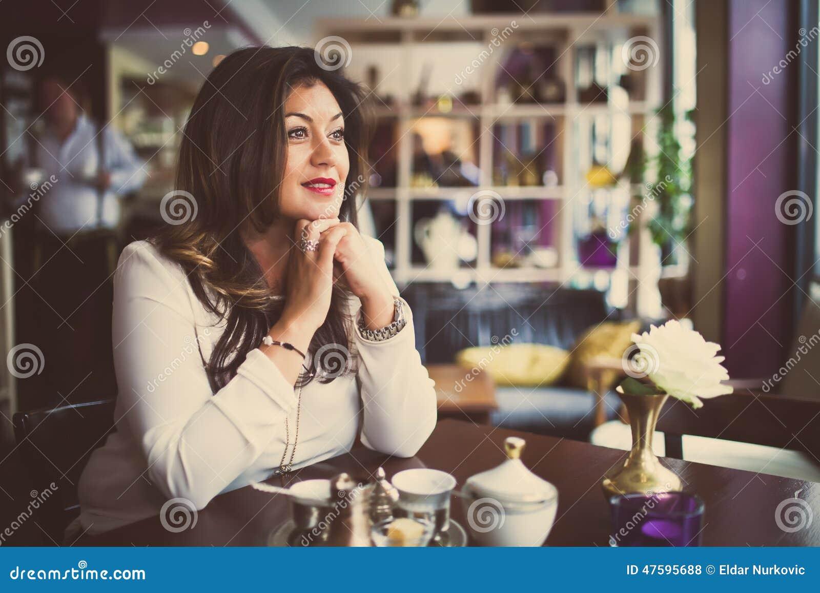 Donna di bellezza che gode della bevanda dopo il lavoro Il bello mezzo sorridente ha invecchiato la donna che si siede da solo in