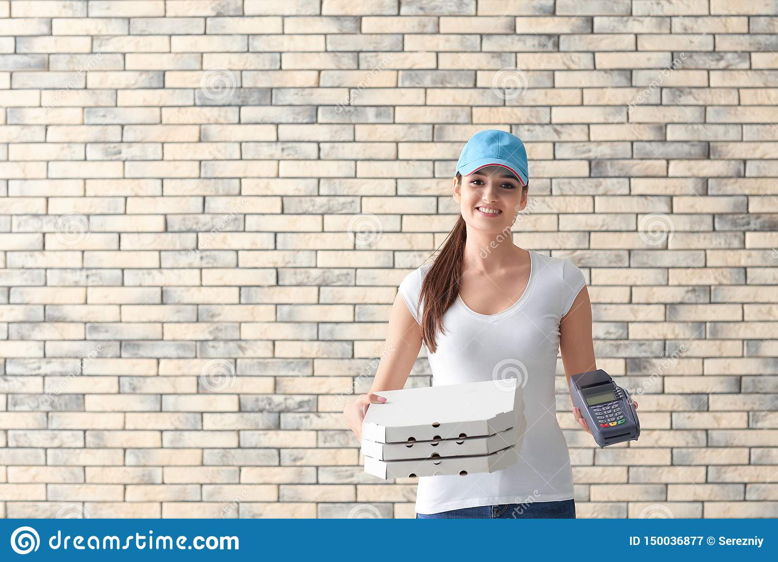 Donna di consegna con i contenitori di pizza del cartone ed il terminale di pagamento sul fondo del muro di mattoni