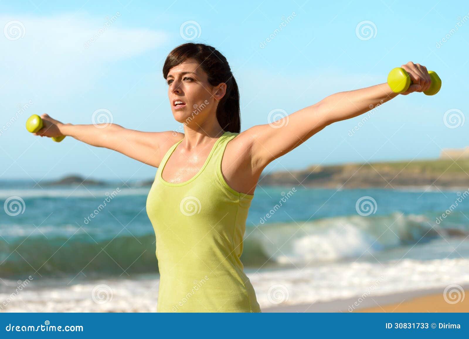 Donna di forma fisica che risolve sulla spiaggia