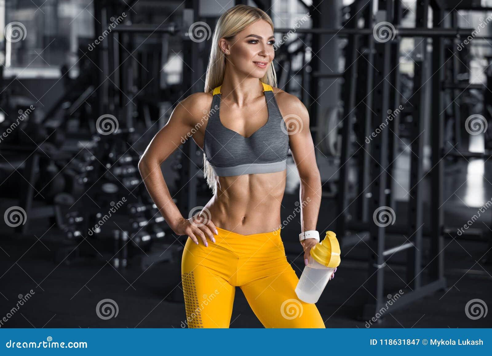 Donna di forma fisica con l agitatore in palestra, acqua potabile Ragazza atletica, vita addominale e esile a forma di