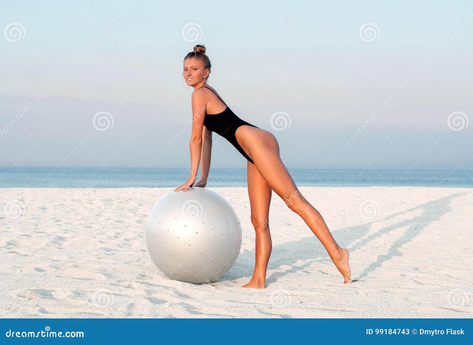 Donna di forma fisica con la palla di misura sulla spiaggia all aperto