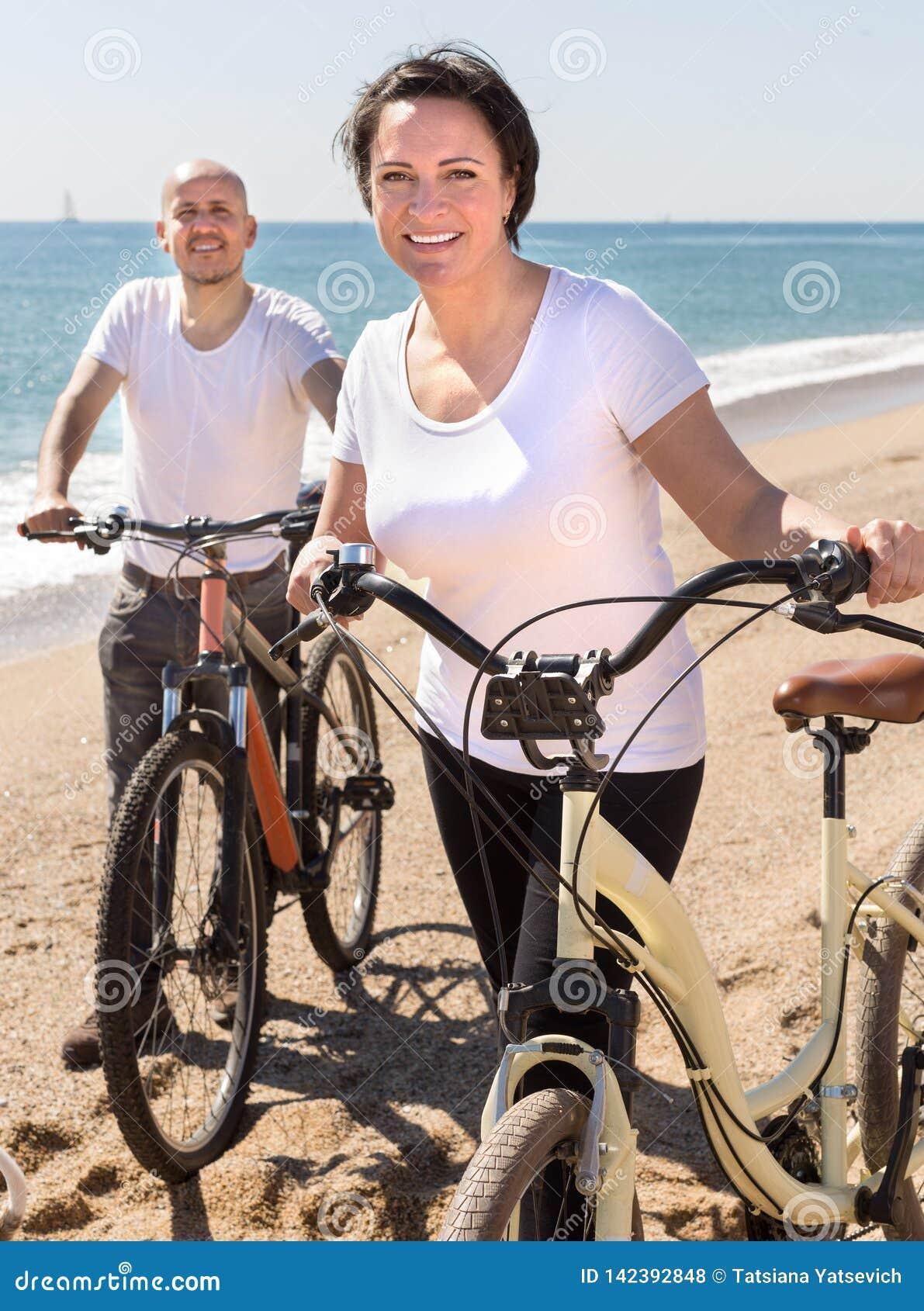 Donna di mezza età ed uomo con le biciclette che camminano sulla spiaggia