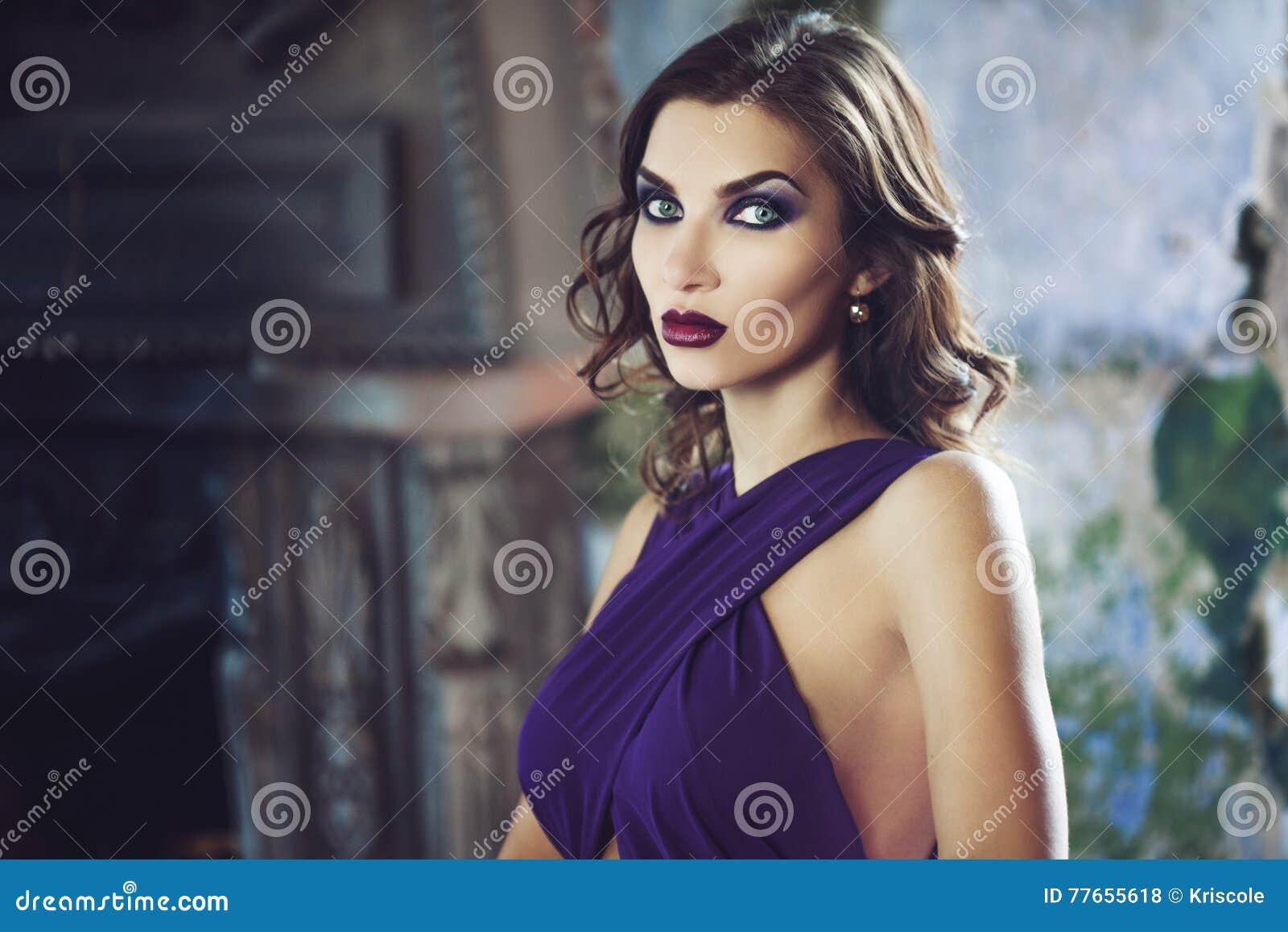 Donna di modello castana di bellezza nell uguagliare vestito porpora Trucco di lusso e acconciatura di bello modo