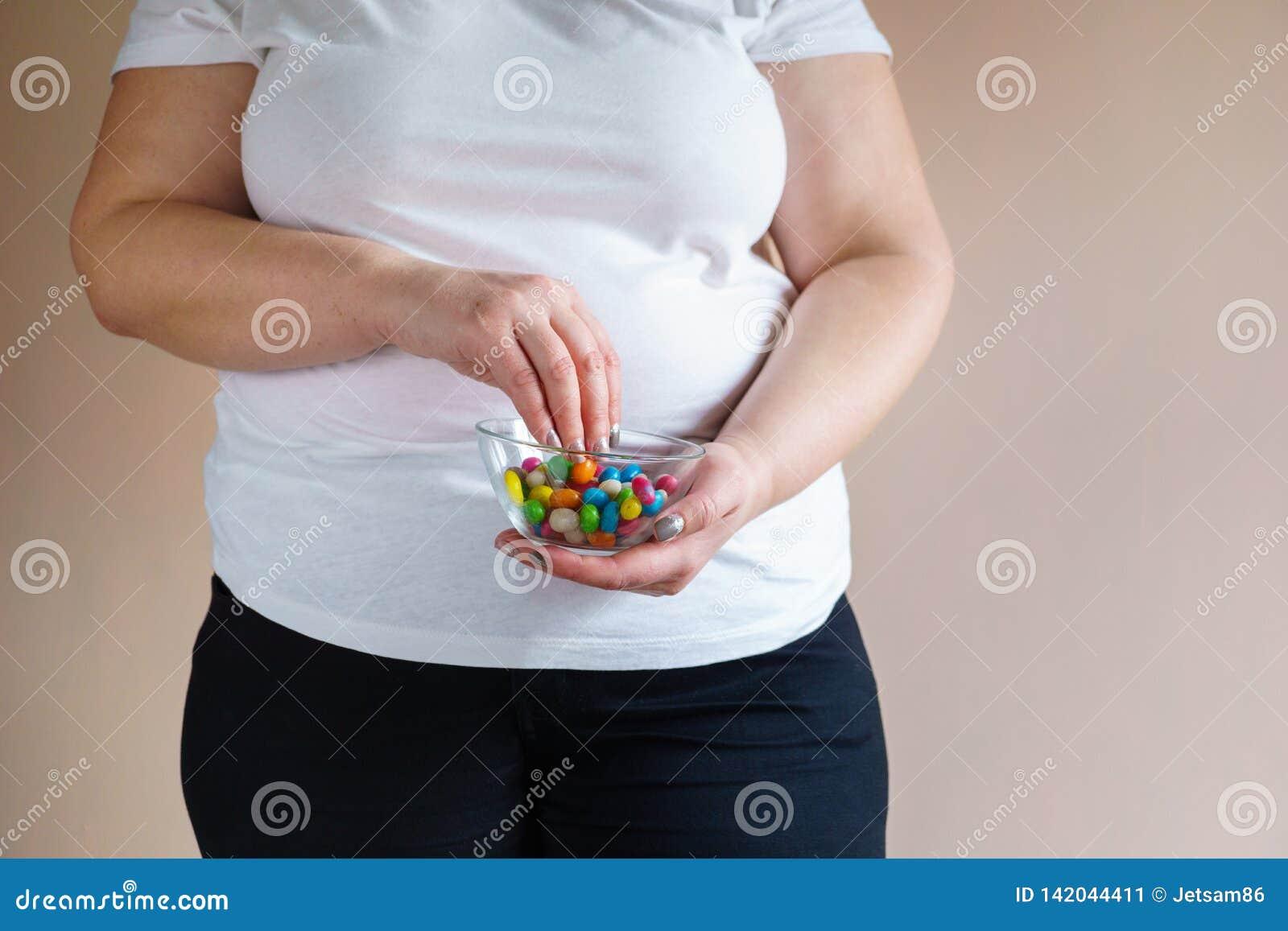 Donna di peso eccessivo che mangia le caramelle dolci non sane