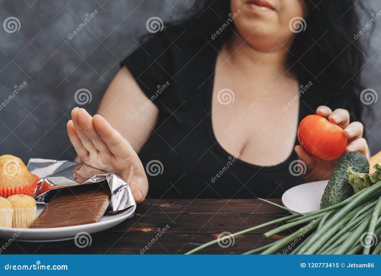 Donna di peso eccessivo che rifiuta la barra di cioccolato
