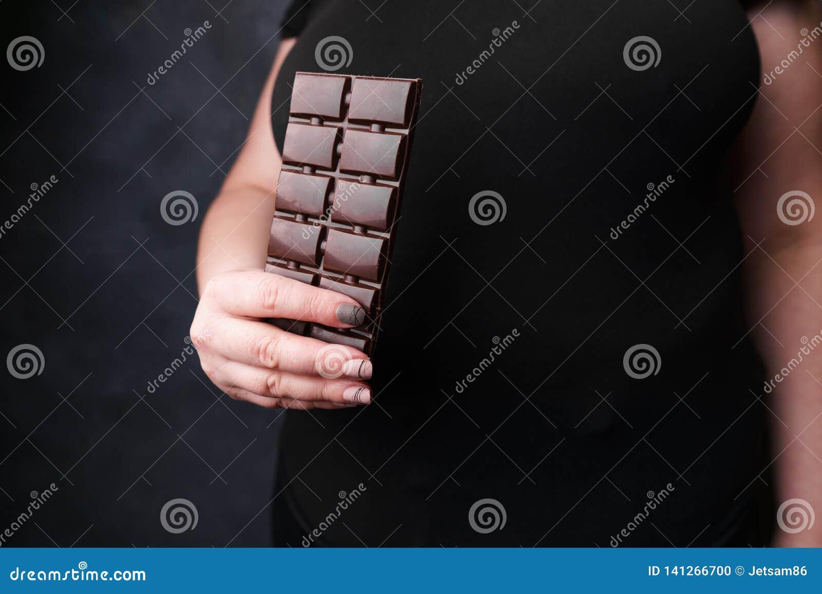 Donna di peso eccessivo con la barra di cioccolato Perdita di peso