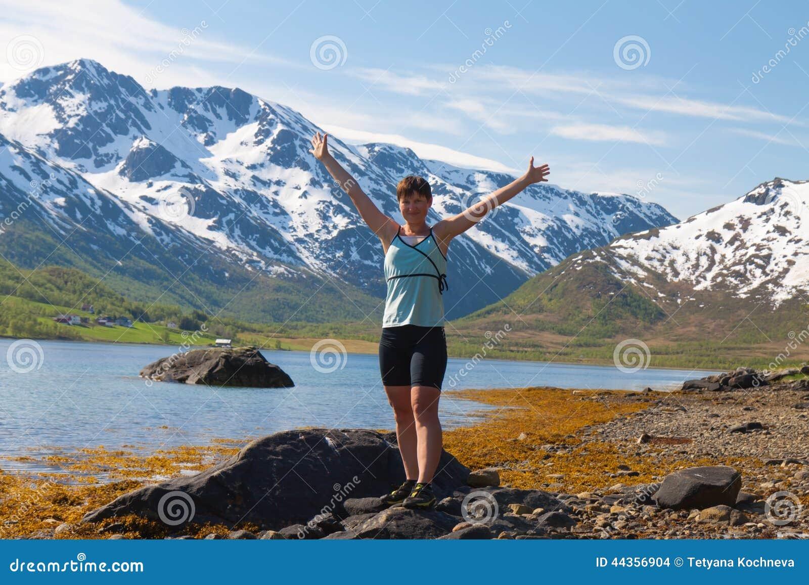 Donna di sport vicino al lago della montagna
