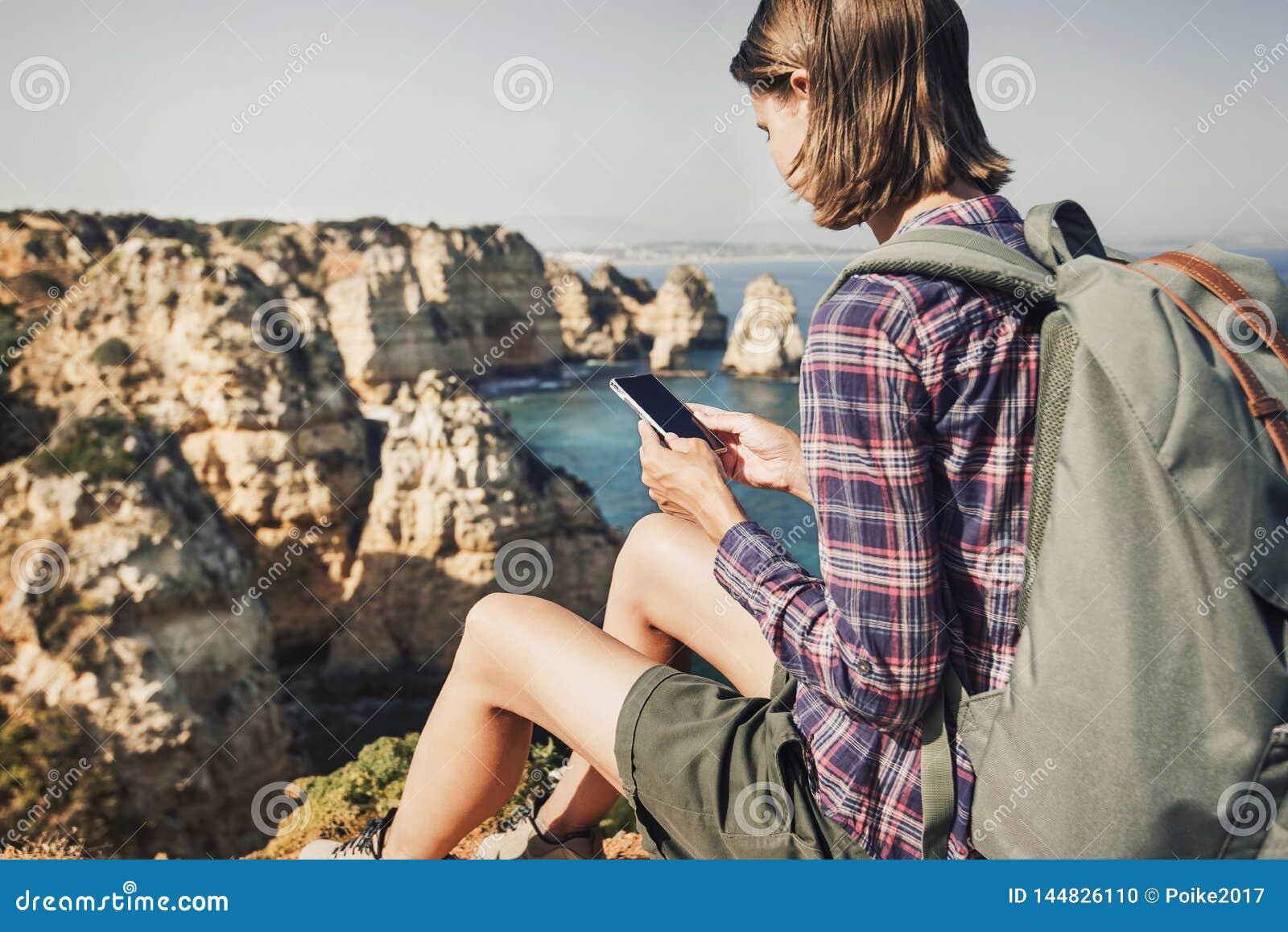 Donna di viaggio su una traccia di escursione facendo uso dello smartphone, del viaggio e del concetto attivo di stile di vita