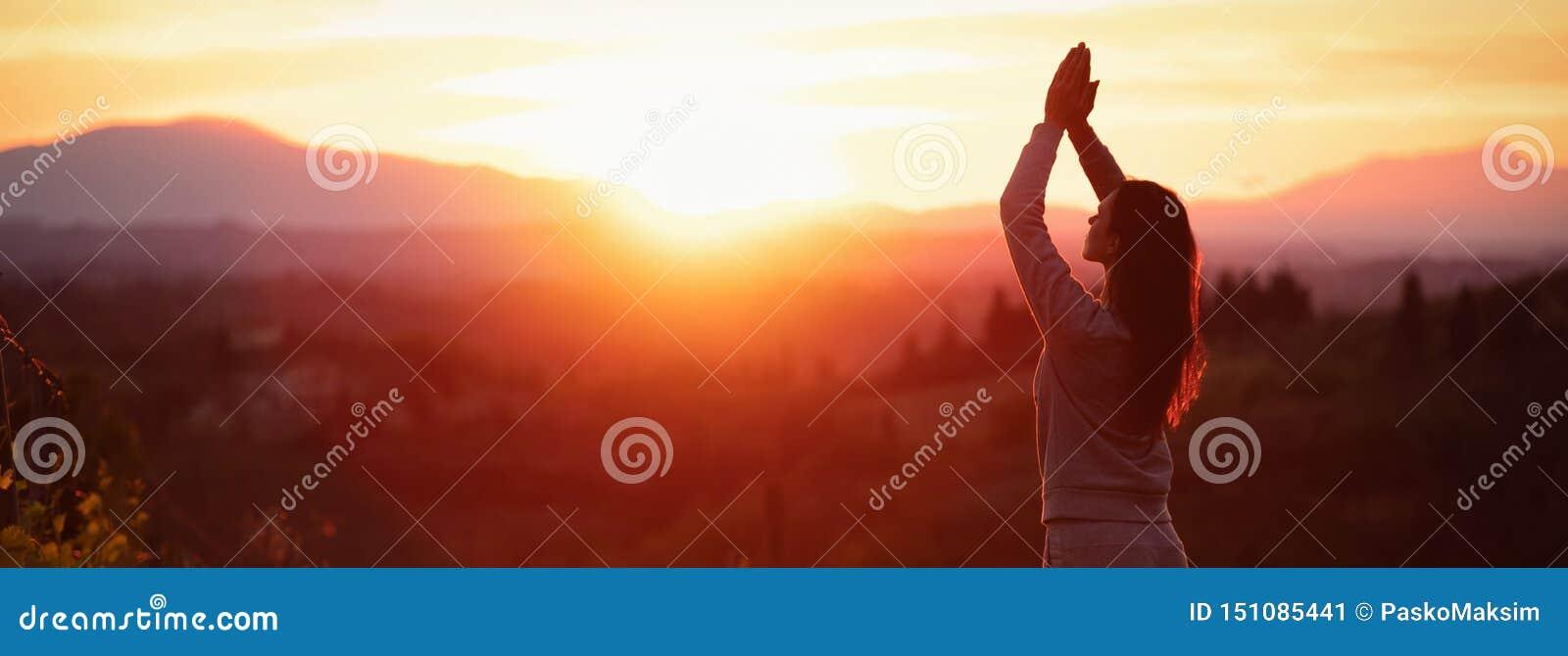 Donna di yoga che medita al tramonto