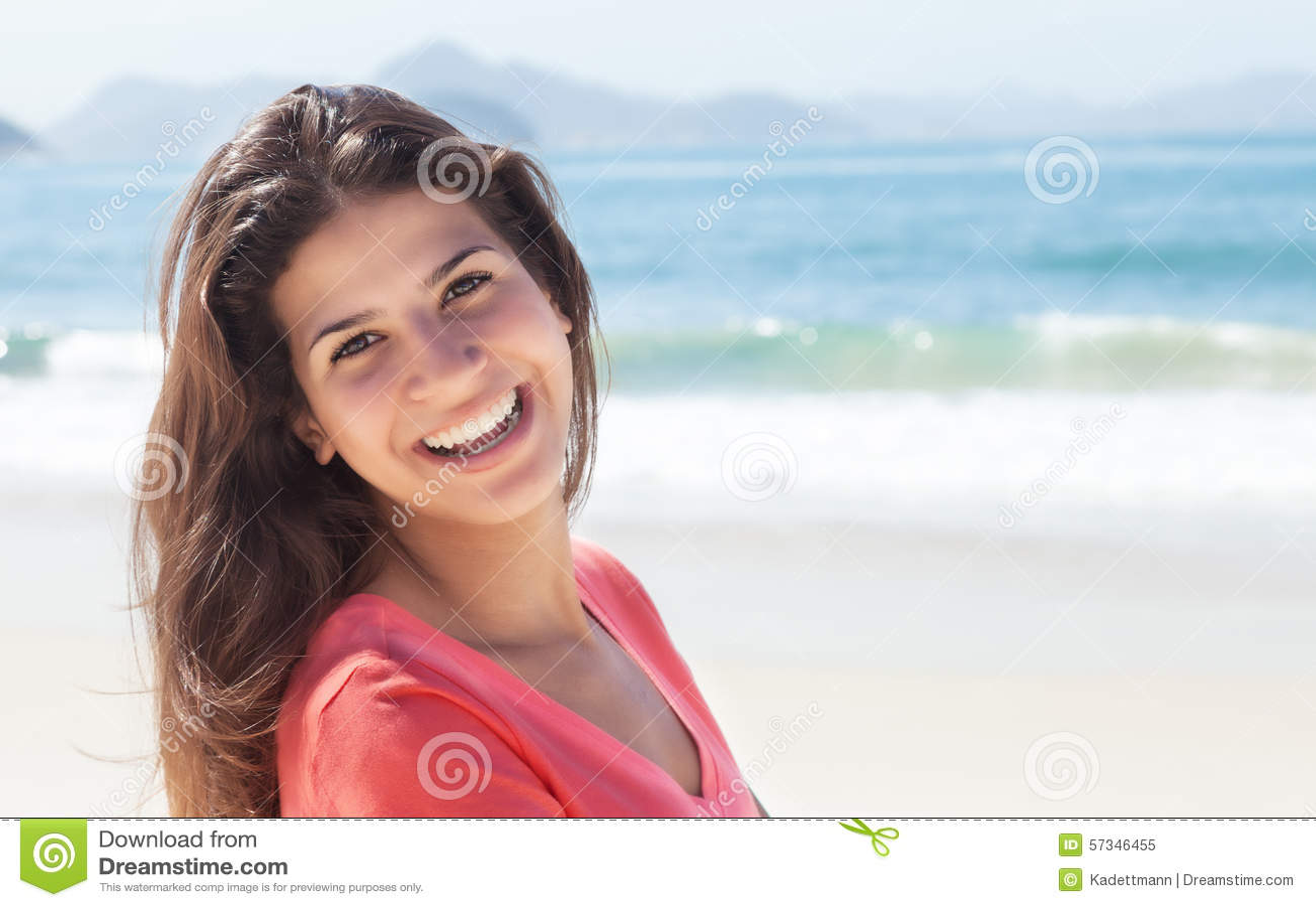 Donna divertente con capelli scuri alla spiaggia