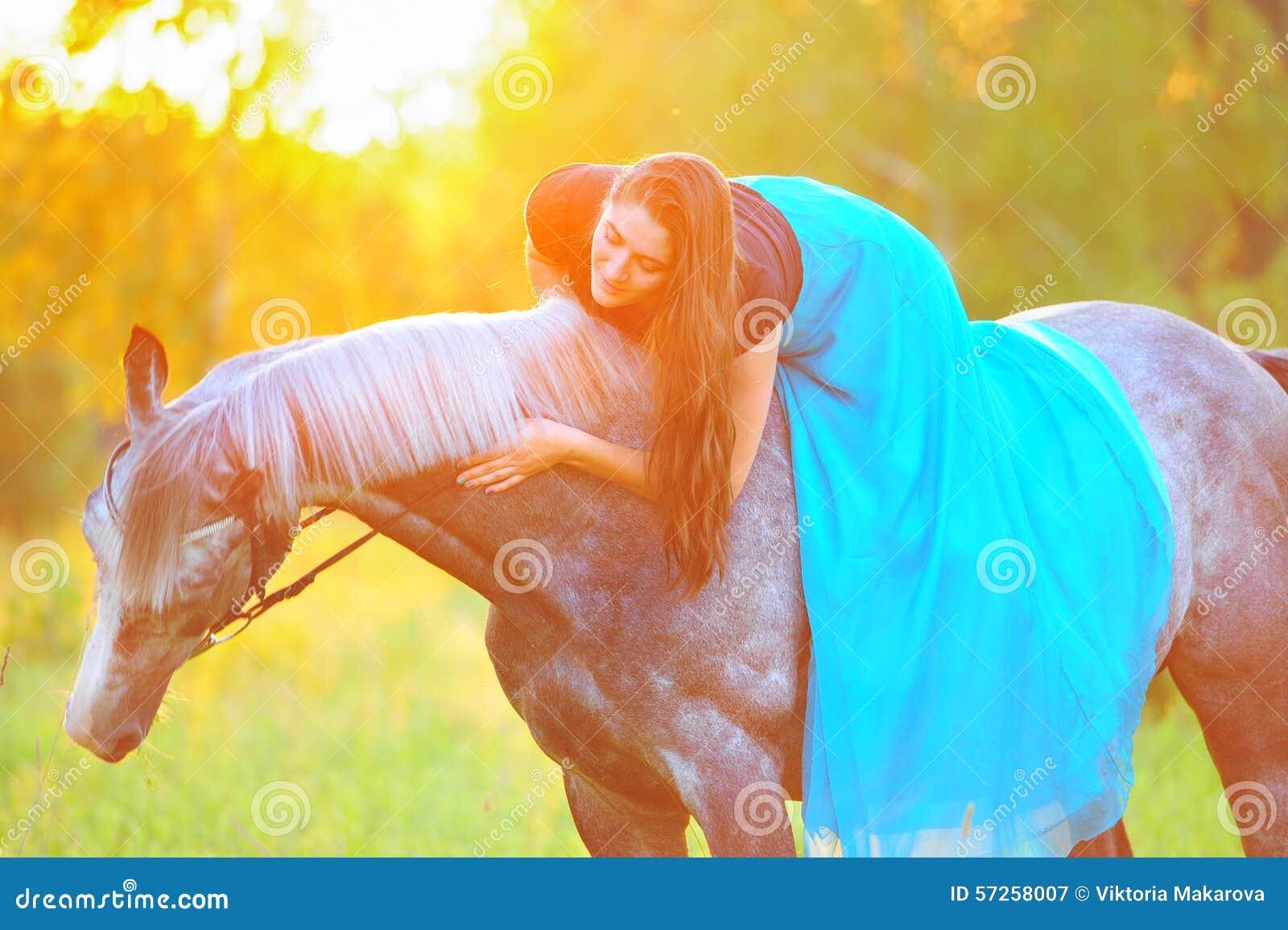 Donna e cavallo grigio alla luce dorata