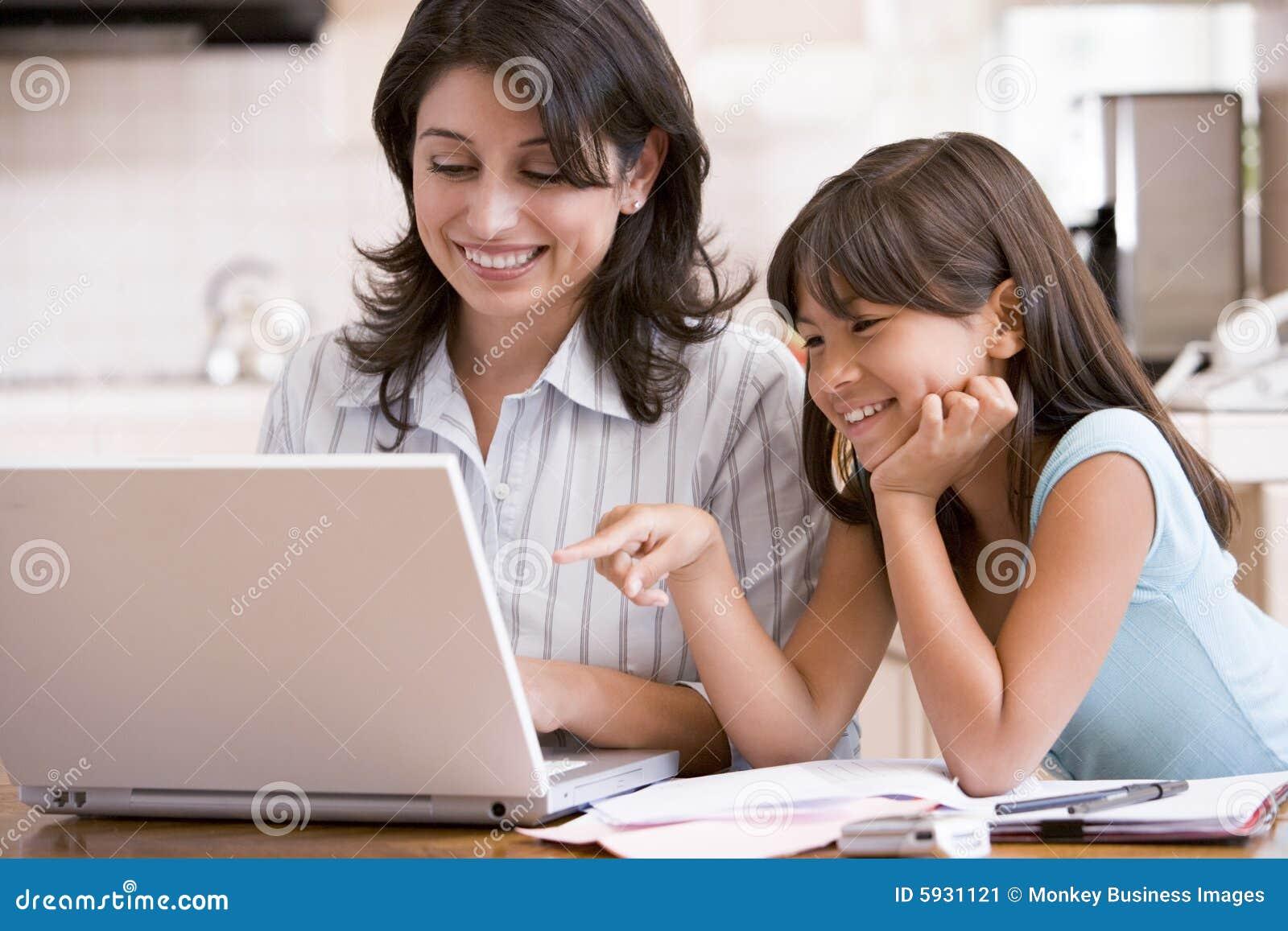 Donna e ragazza in cucina con il computer portatile