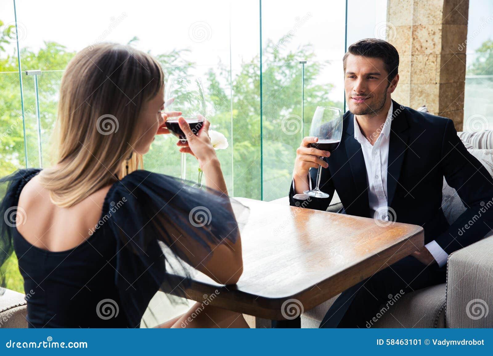 Donna ed uomo sicuro che bevono vino rosso