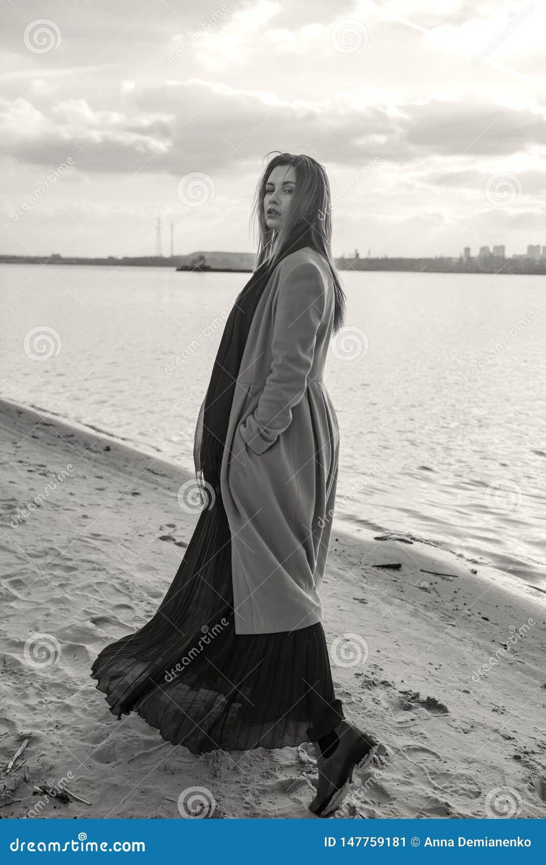 Donna europea splendida in cappotto e vestito caldi su una passeggiata in parco vicino al fiume Tempo ventoso I suoi vestiti vola