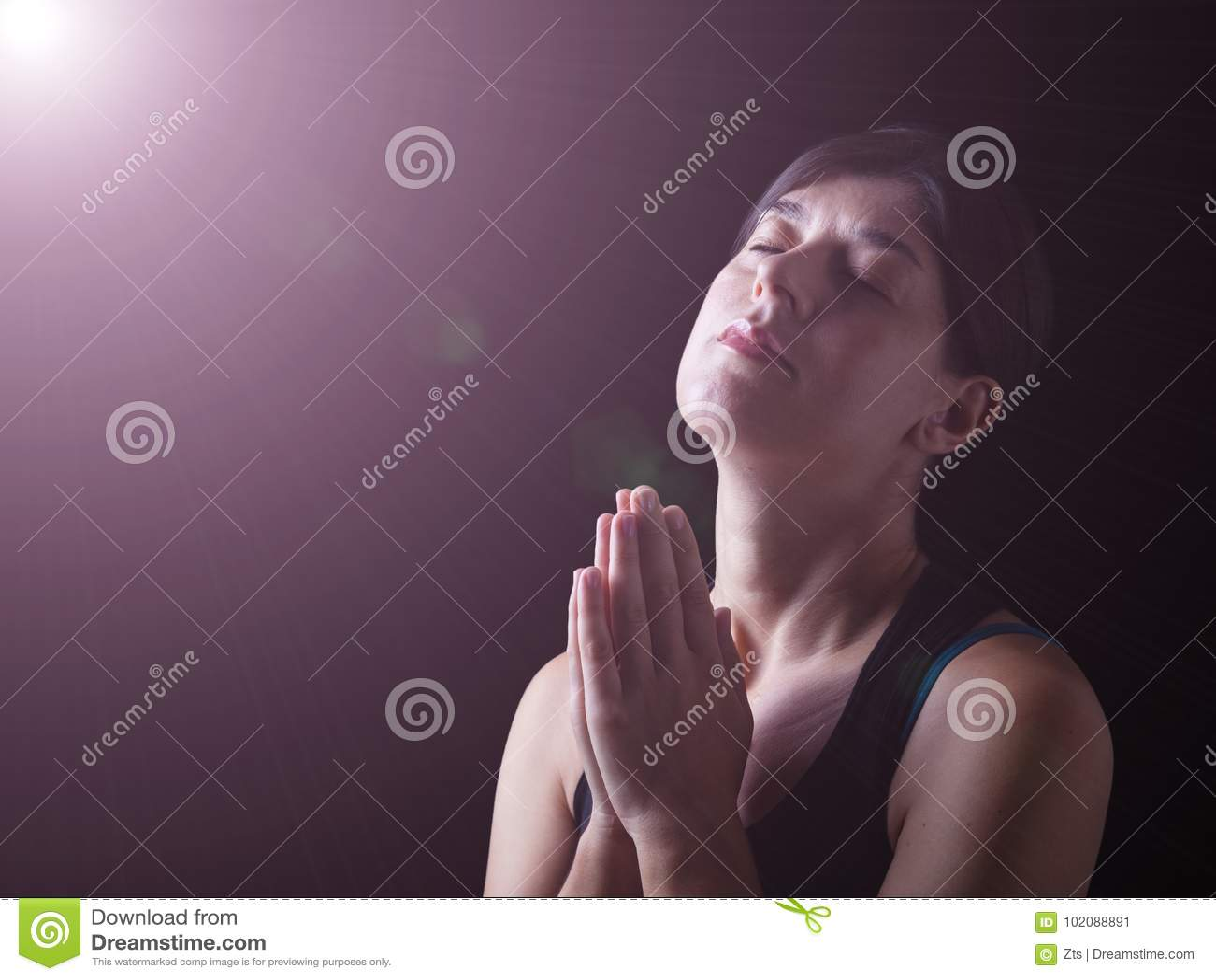 Donna fedele che prega nell ambito di una luce divina o celeste