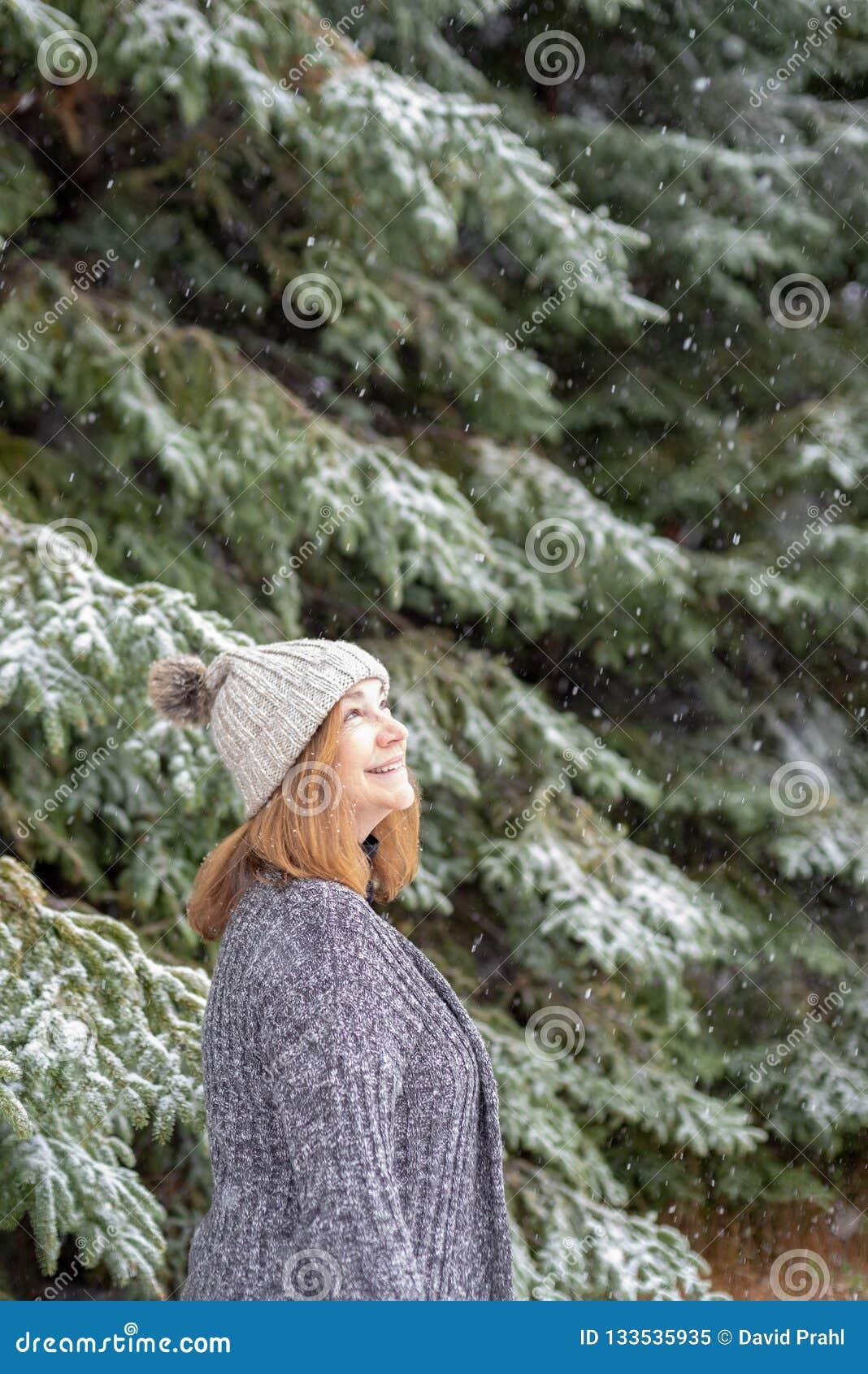 Donna felice che cerca caduta della neve
