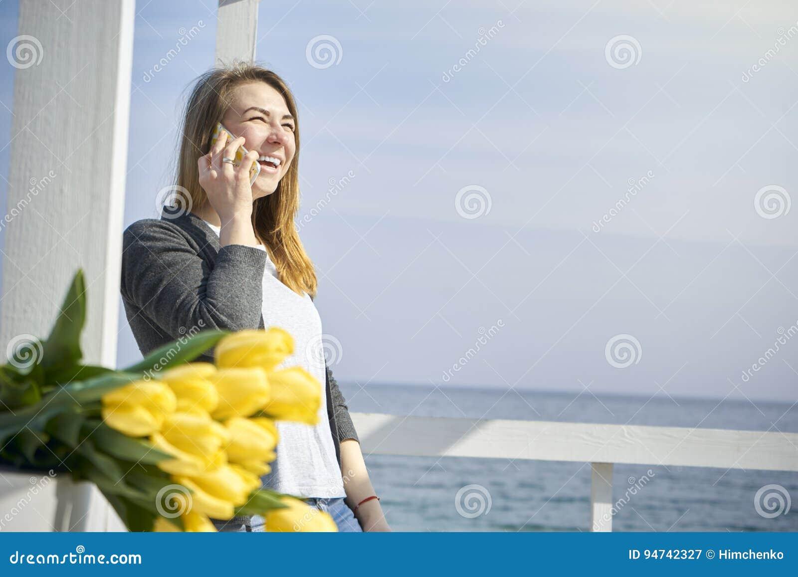Donna felice che comunica sul telefono