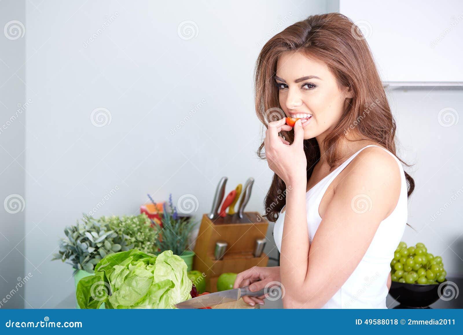 Donna felice che cucina un pasto nella cucina