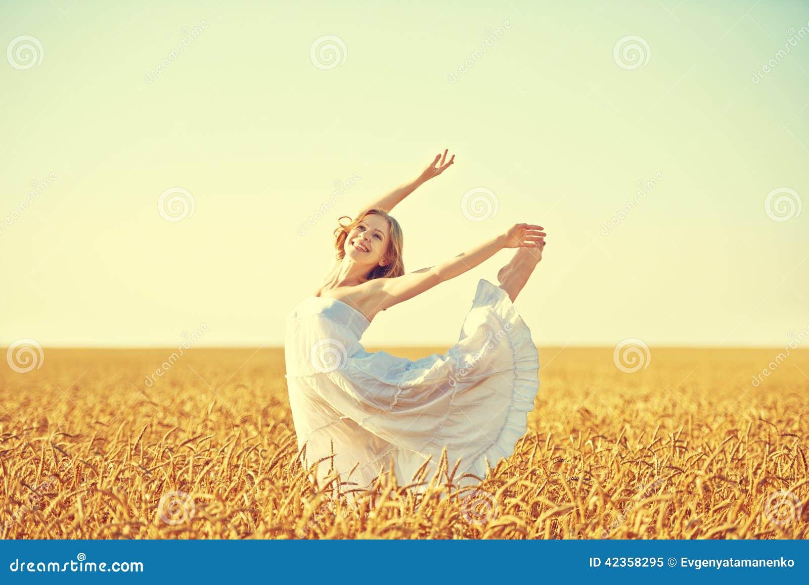 Donna felice che gode della vita nel giacimento di grano dorato