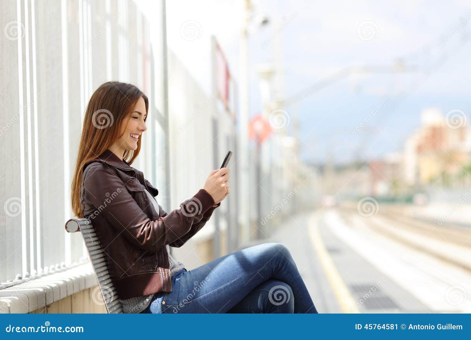 Donna felice che manda un sms su uno Smart Phone in una stazione ferroviaria