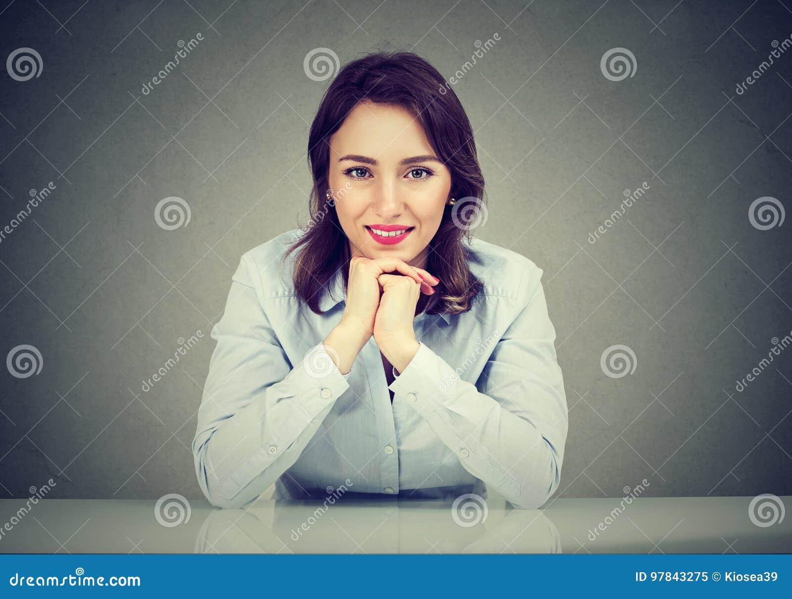 Donna felice che pende alla tavola che sorride alla macchina fotografica