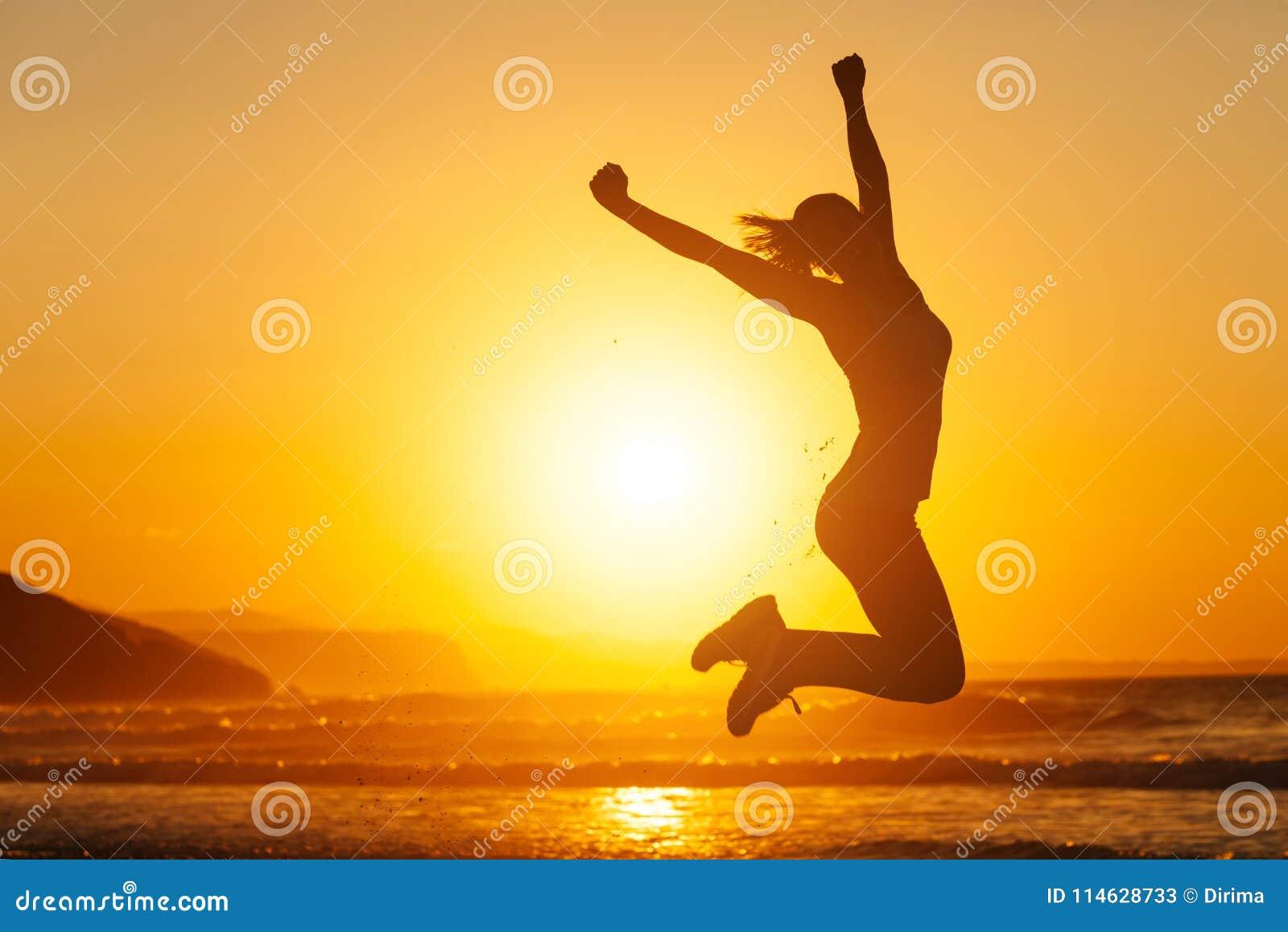Donna felice che salta e che si diverte alla spiaggia