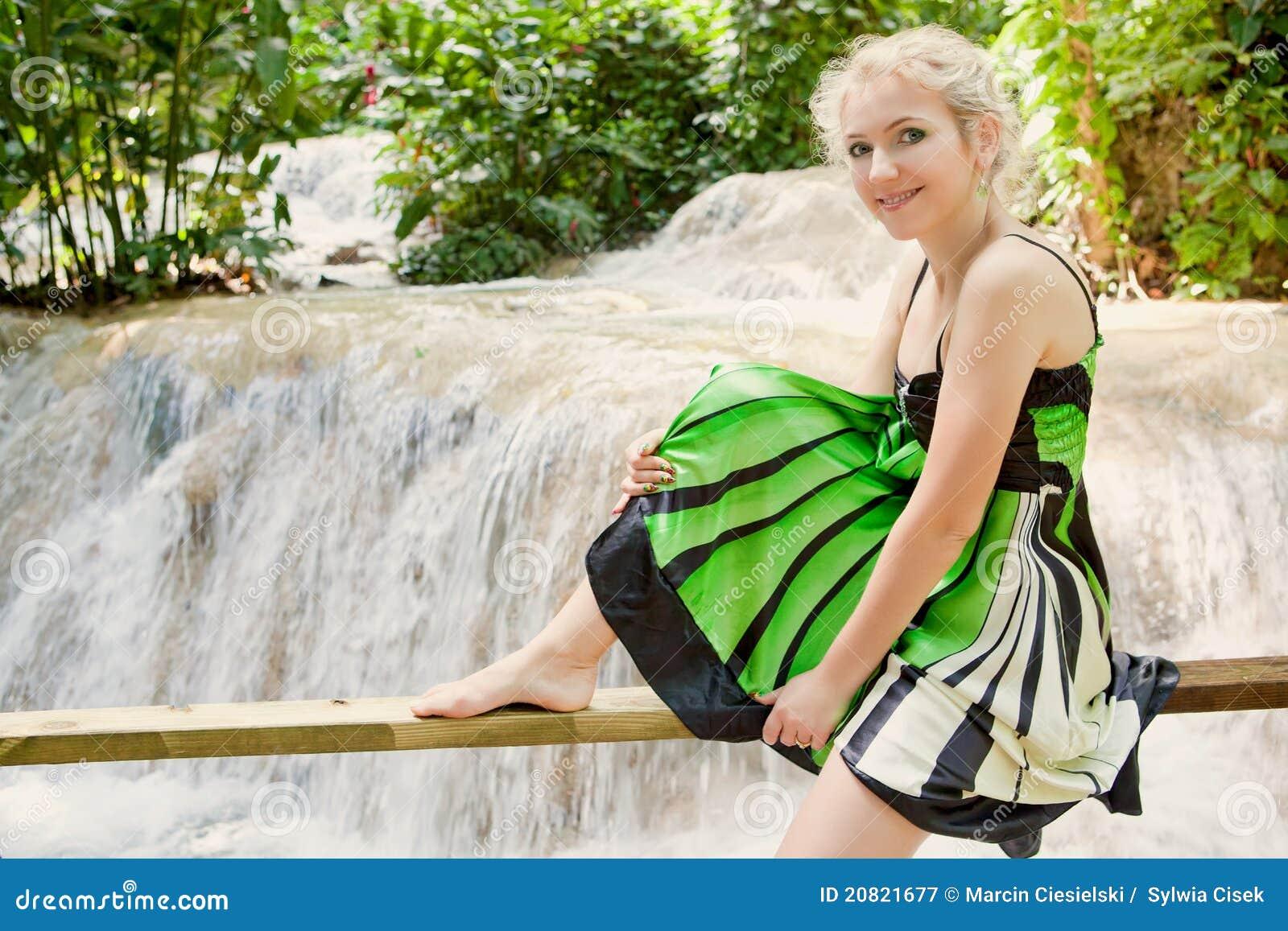 Donna felice che si distende davanti ad una cascata
