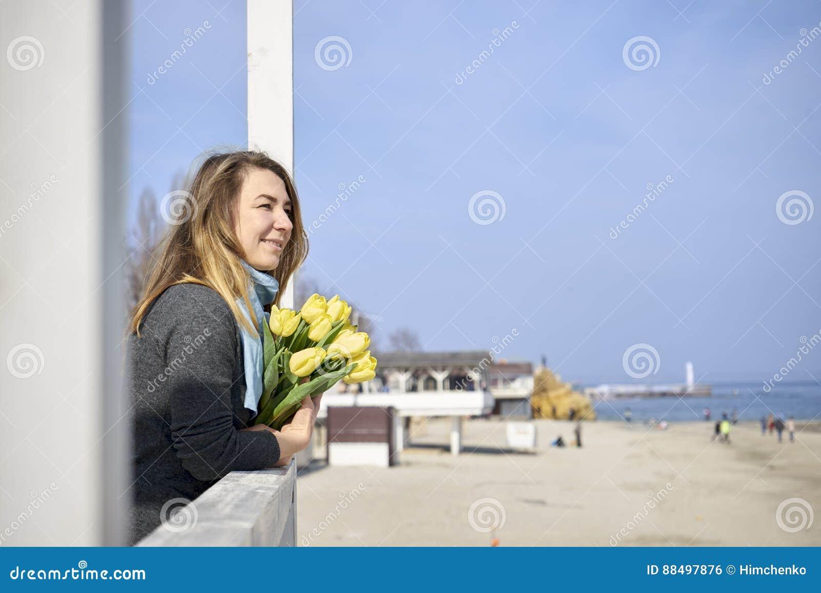 Donna felice con i fiori vicino alla riva di mare