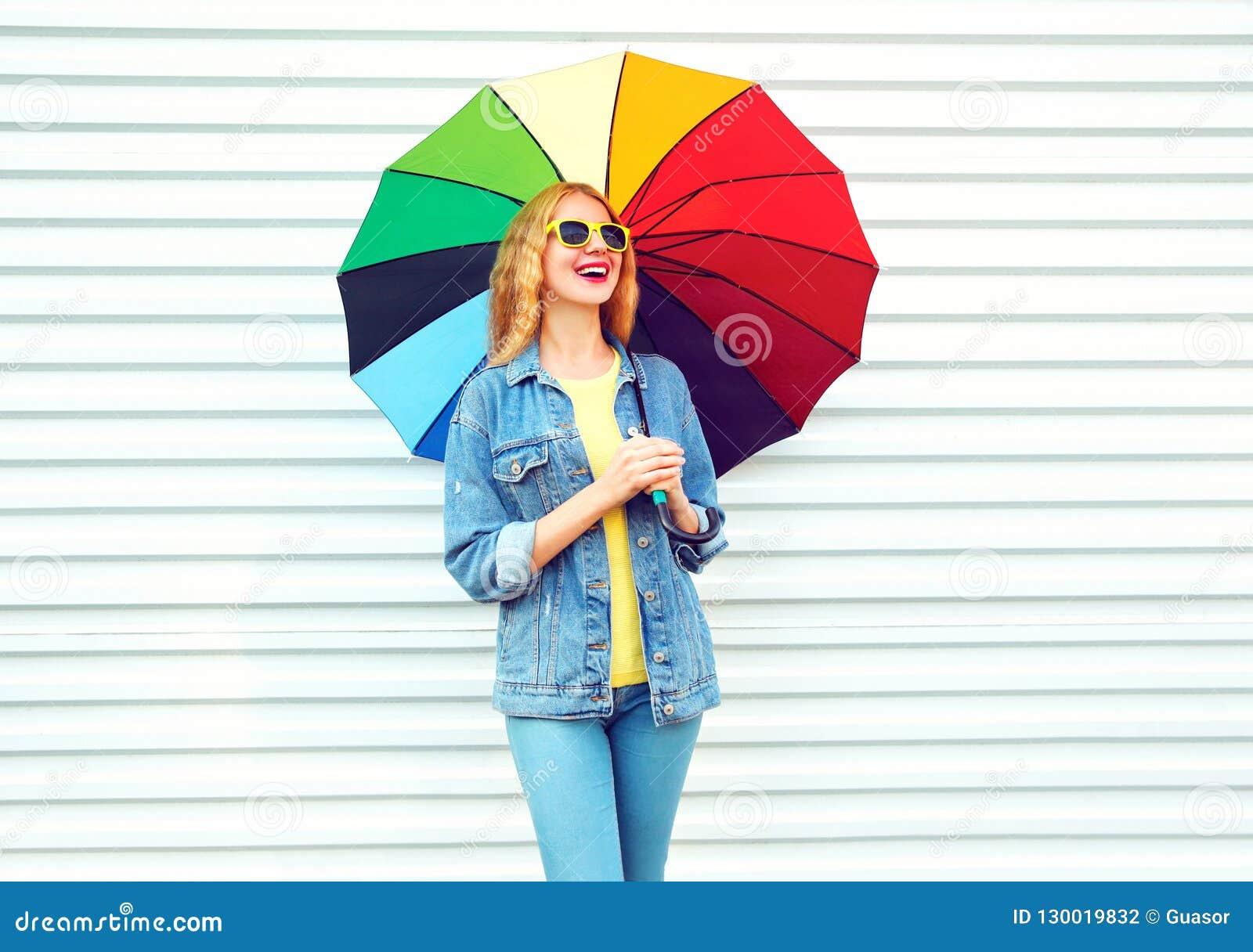 Donna felice di modo che ride con l ombrello variopinto, sogni su bianco