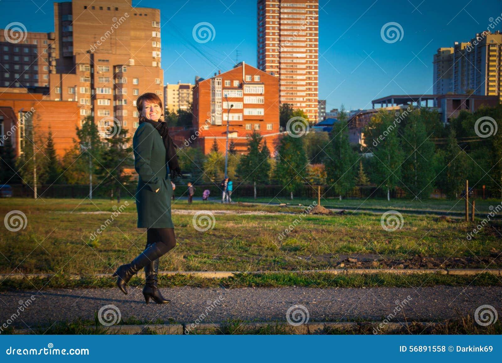 Donna felice in un cappotto scuro che cammina all aperto autunno al tramonto