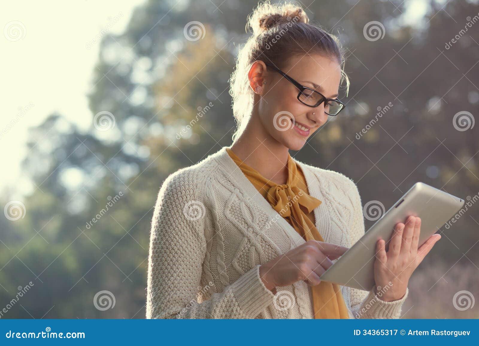 Donna felice in vetri facendo uso del pc della compressa