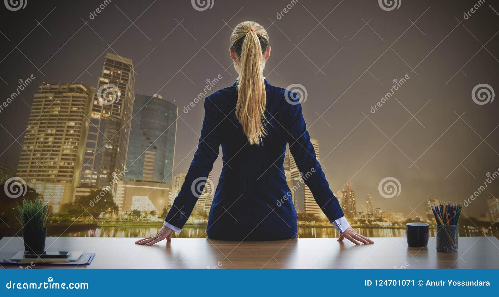 Donna femminile di affari che guarda fuori le finestre di notte della città per