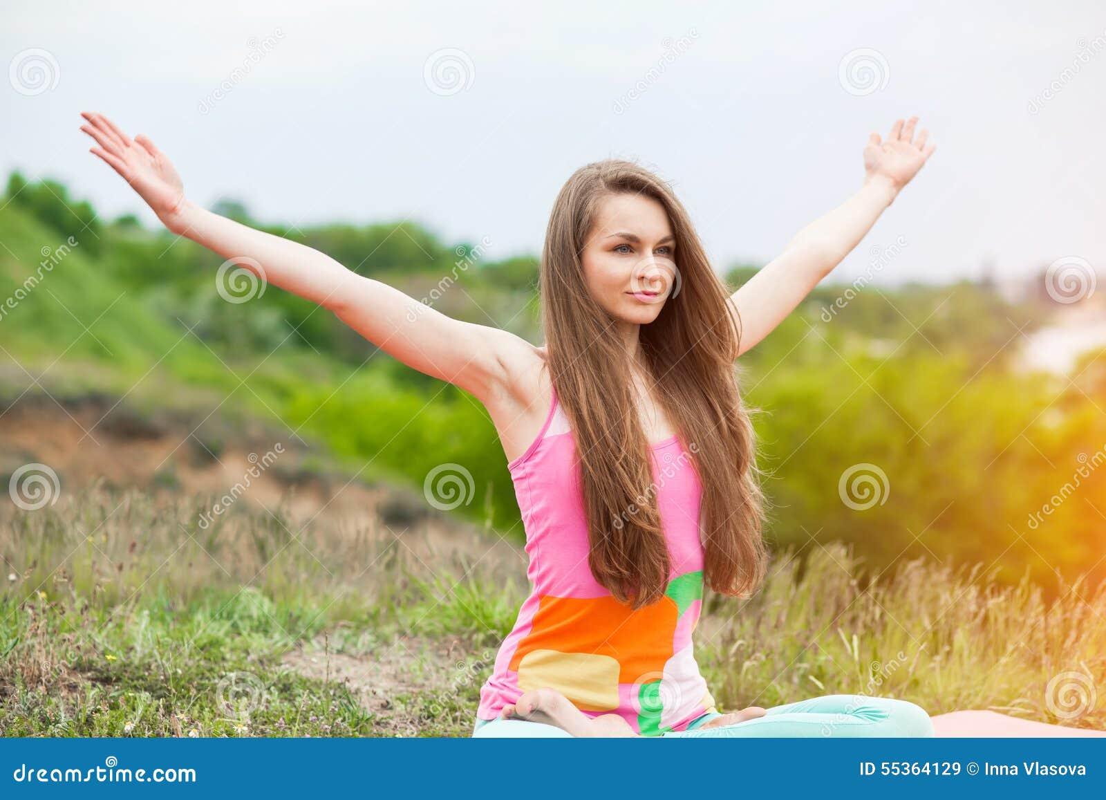 Donna graziosa che fa gli esercizi di yoga sul paesaggio della natura
