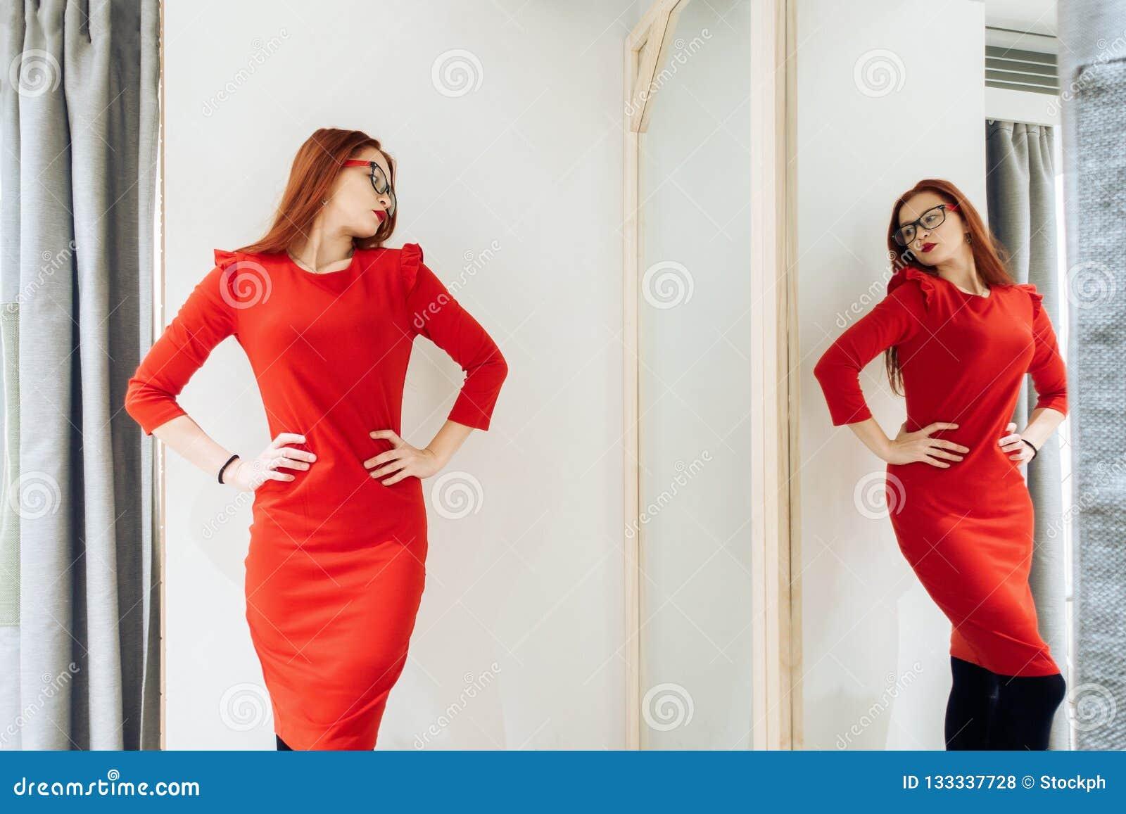 Donna graziosa che prova sui vestiti in un negozio adatto la signora in rosso si veste è riflessa nello specchio