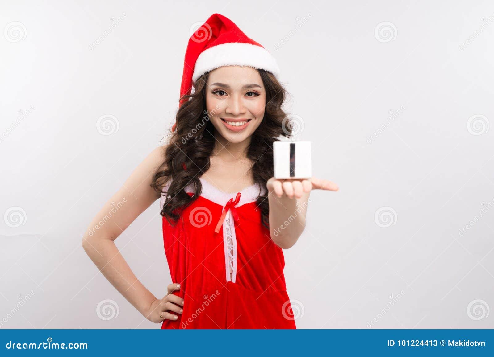 6b5309e77427 Donna graziosa felice in vestito rosso e contenitore di regalo della tenuta  del cappello del Babbo Natale isolati sui precedenti bianchi
