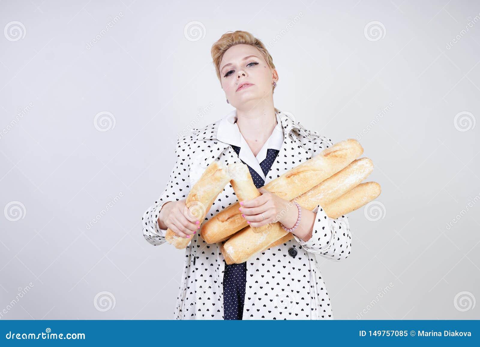 Donna incantante del pinup con i capelli di scarsità in un cappotto della molla con i pois che posano con le baguette e goderle d