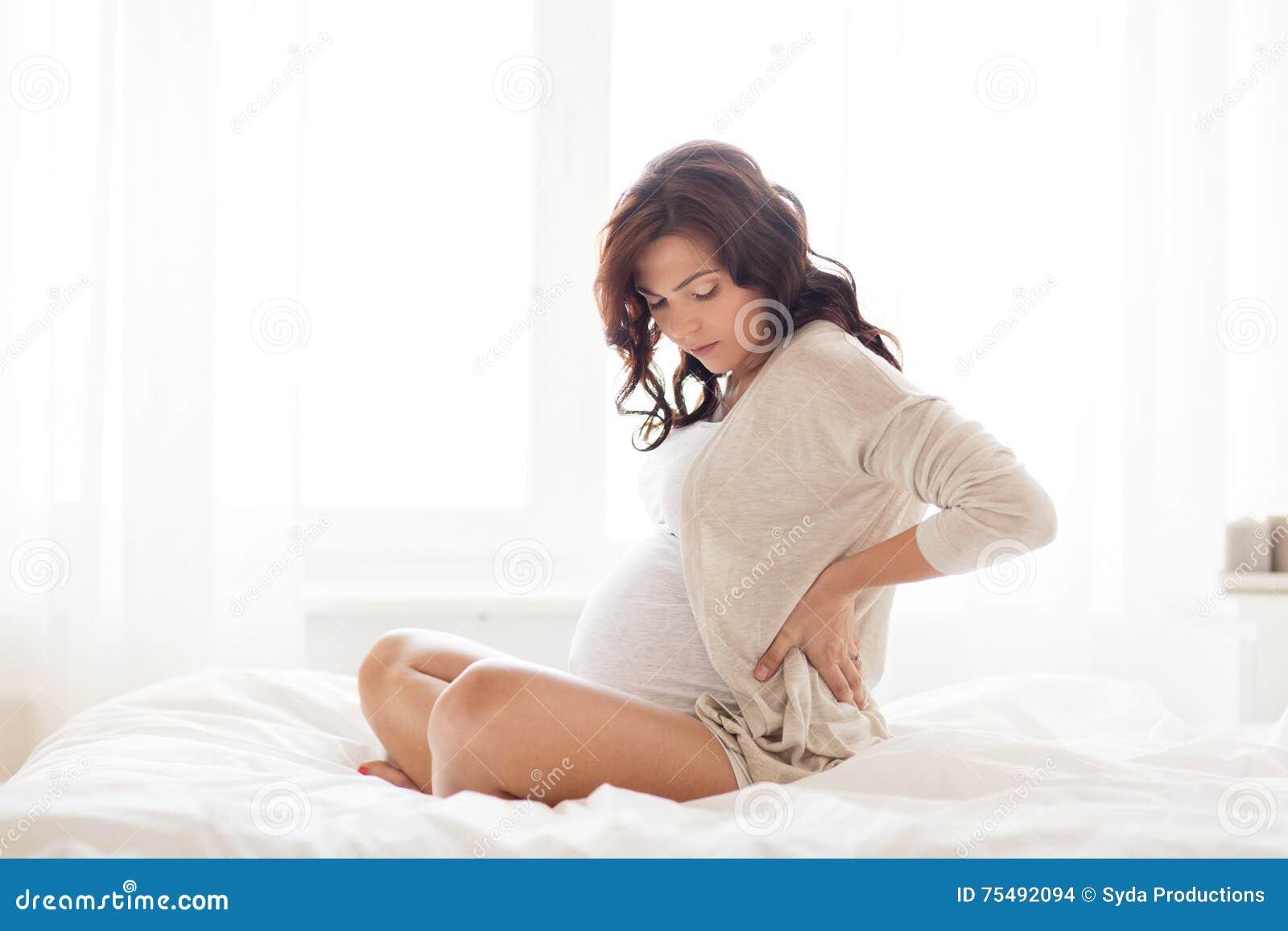 Donna incinta con il mal di schiena a letto a casa - Mal di schiena letto ...