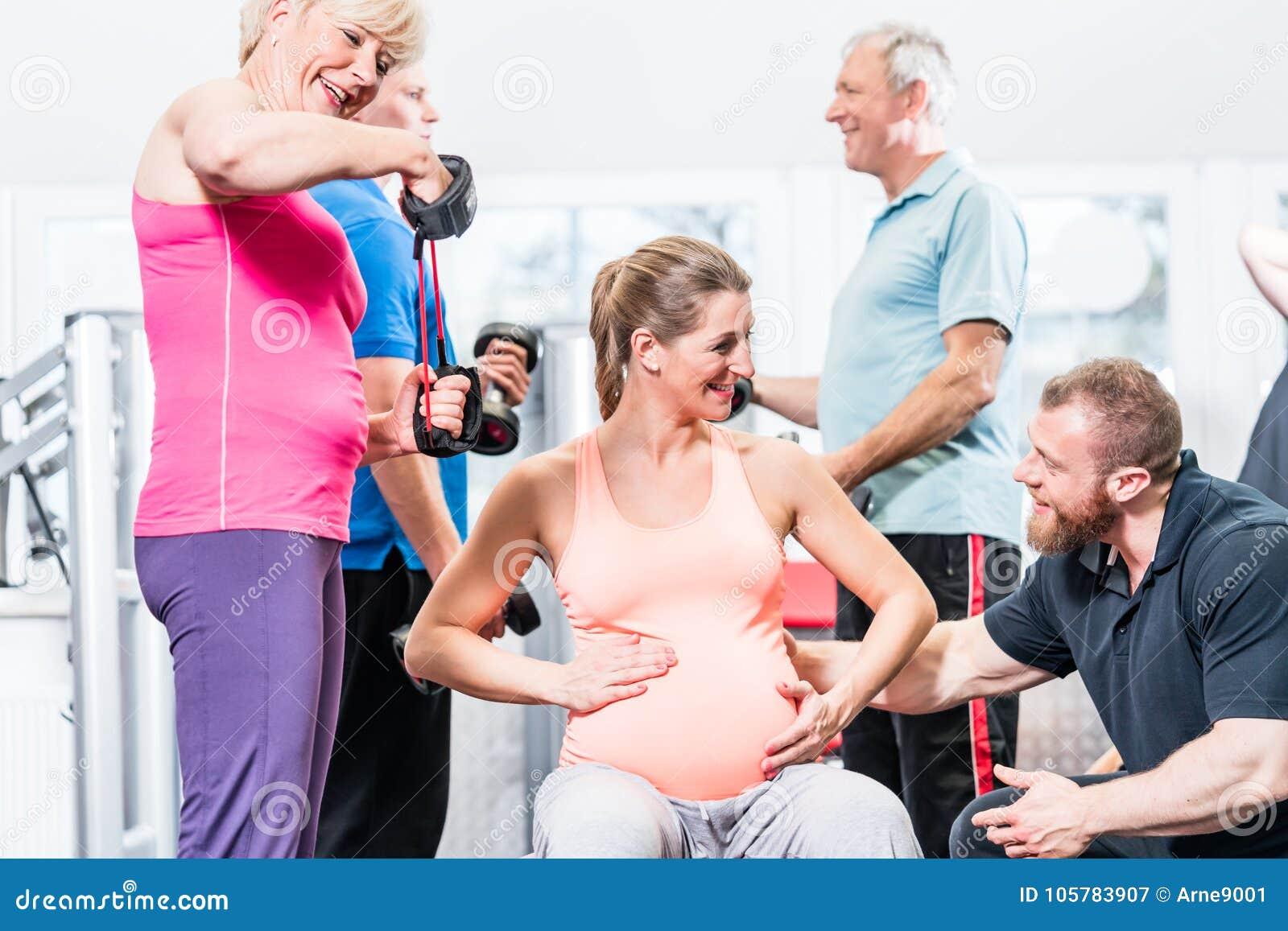 Donna incinta con la gente senior che risolve alla palestra con pe