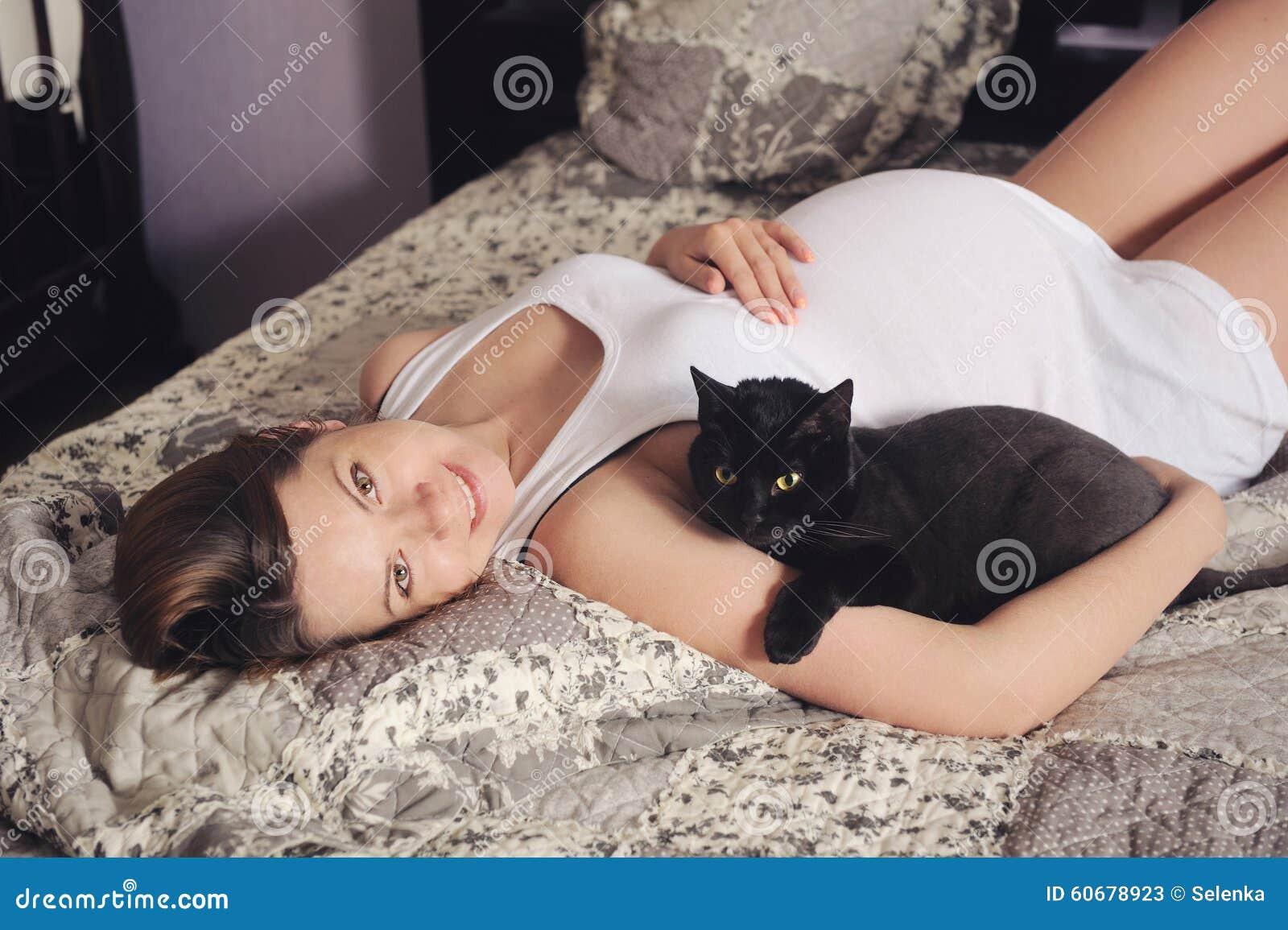 Donna incinta sveglia che si trova a letto con il gatto - A letto con due donne ...