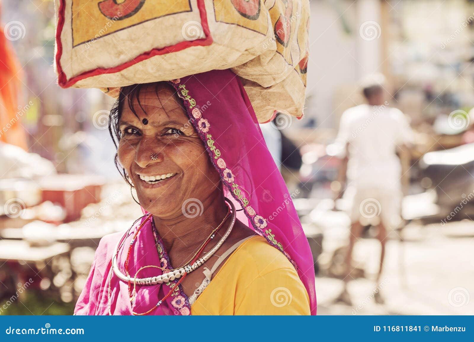 Donna indiana che si preoccupa un sacchetto della spesa sulla sua testa