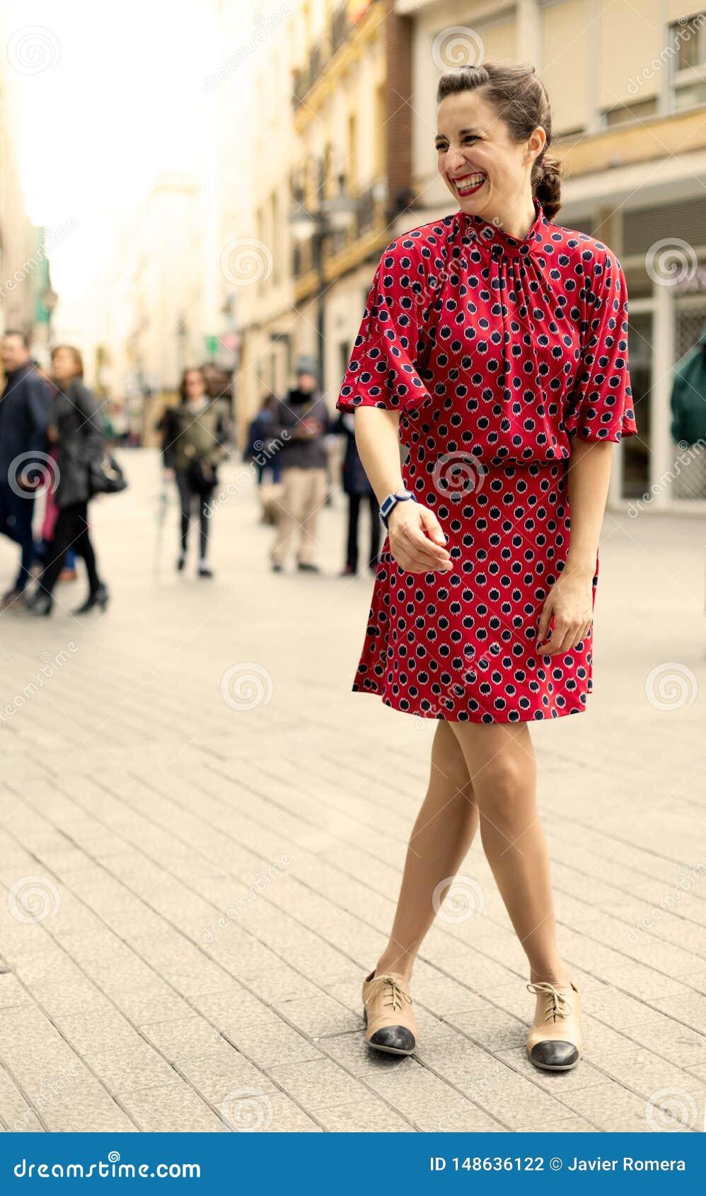 Donna indipendente vestita nel rosso che ride molto con le emozioni positive